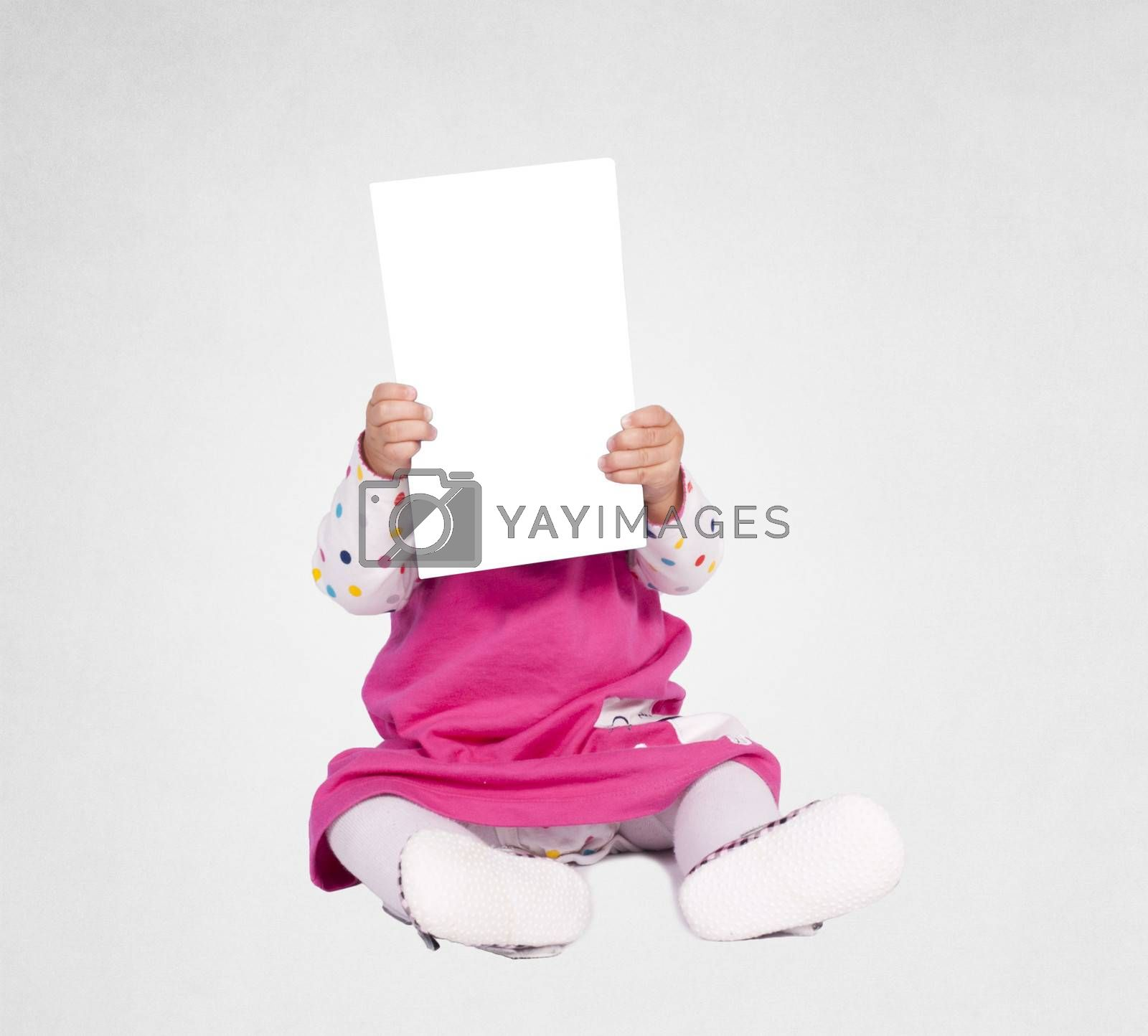 Little baby girl holding blank paper over her head
