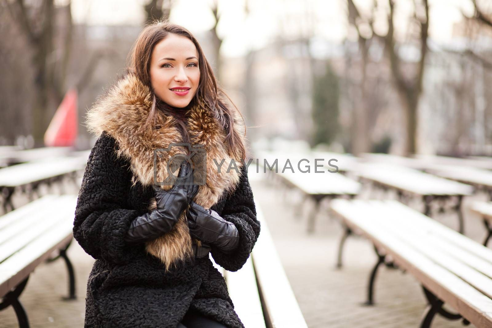 Young woman sitting on the bench in winter park
