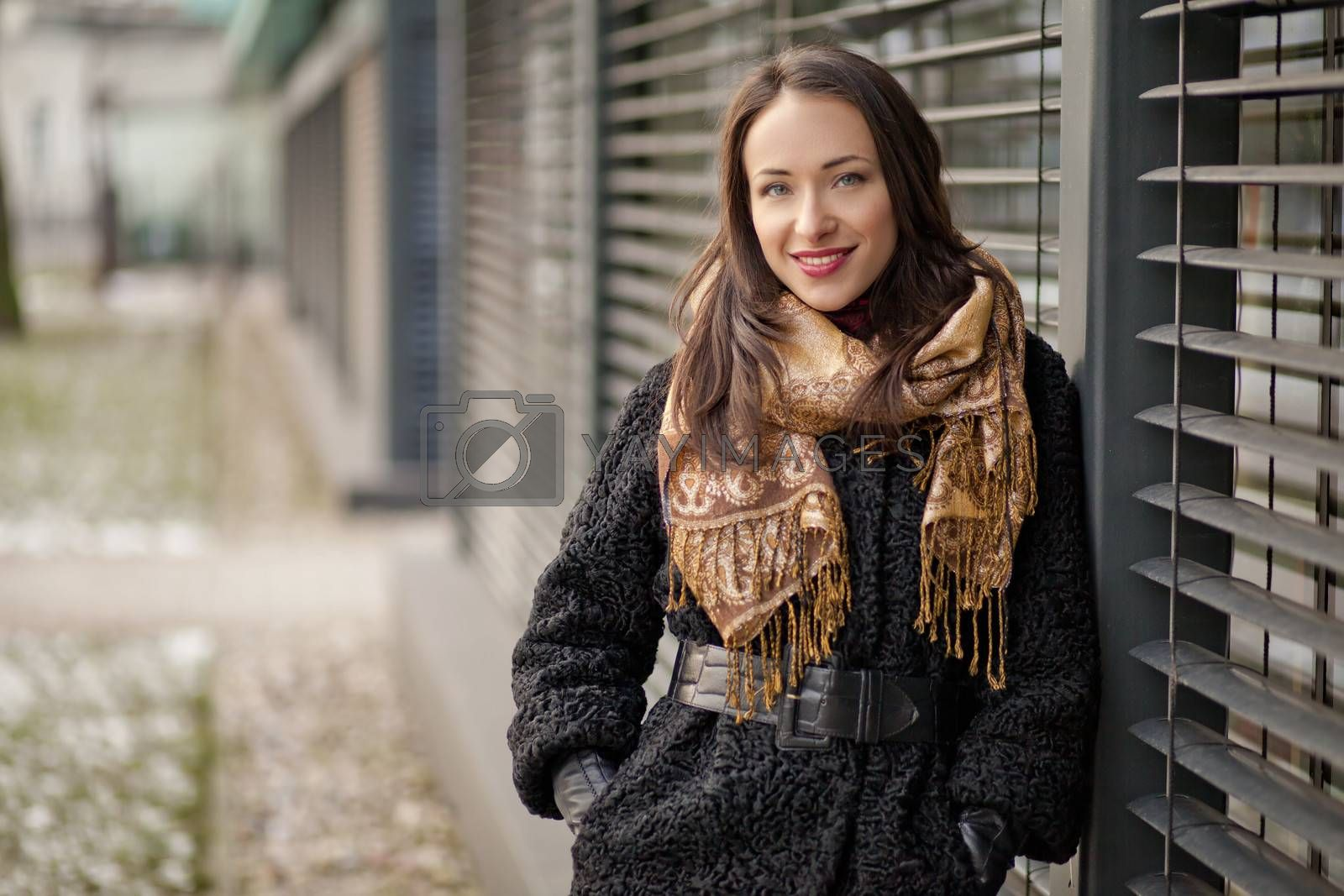 Young pretty lady is standing by the louvers and enjoying winter