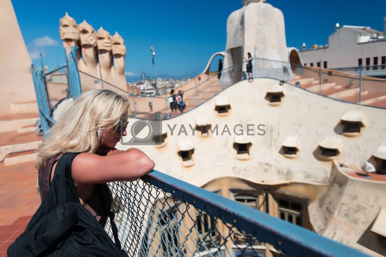 Young blond woman visiting Casa Milo (or La Pedrera) in Barcelona Spain