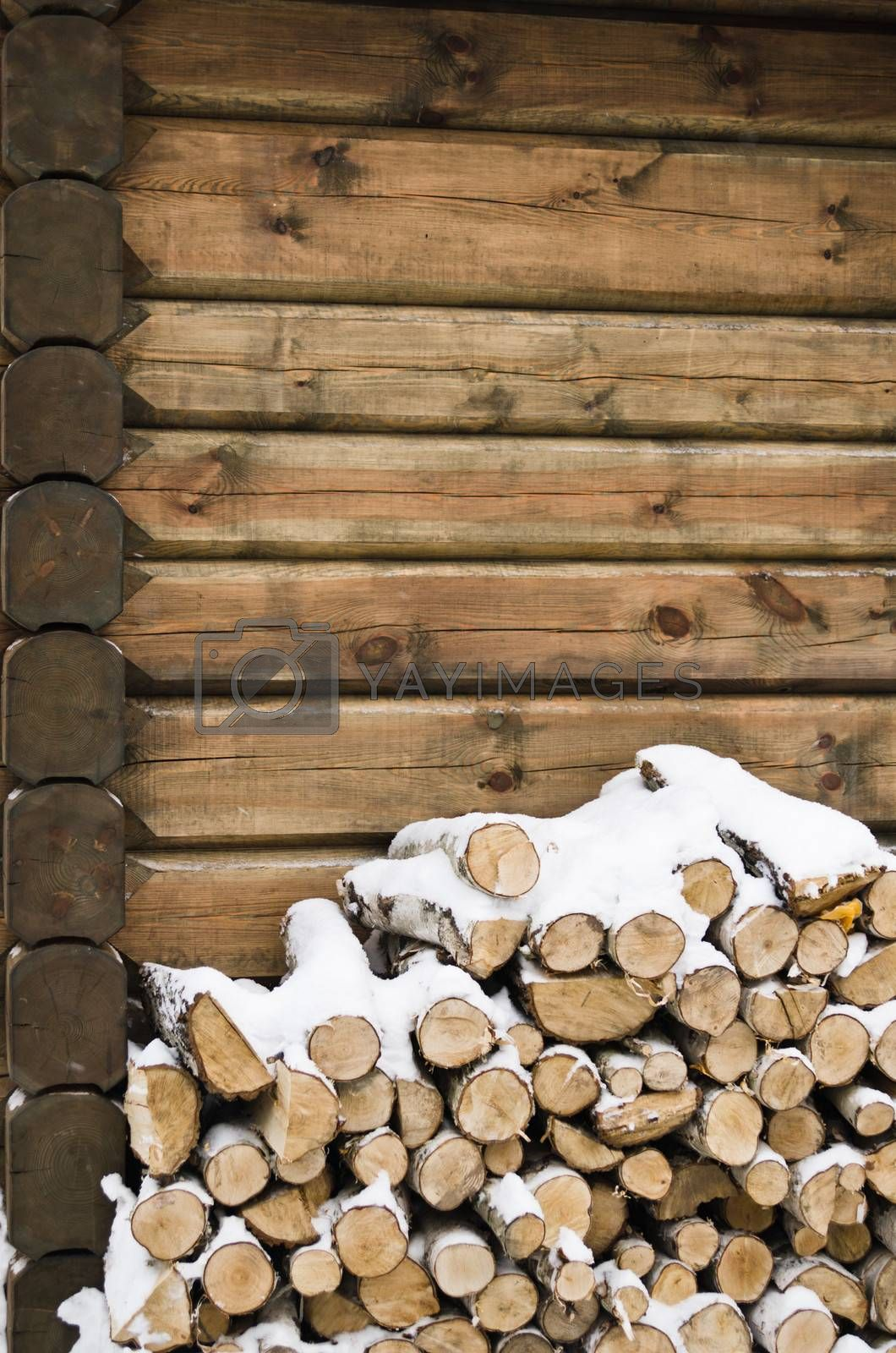 Birch fire wood at a wall of the house in winter