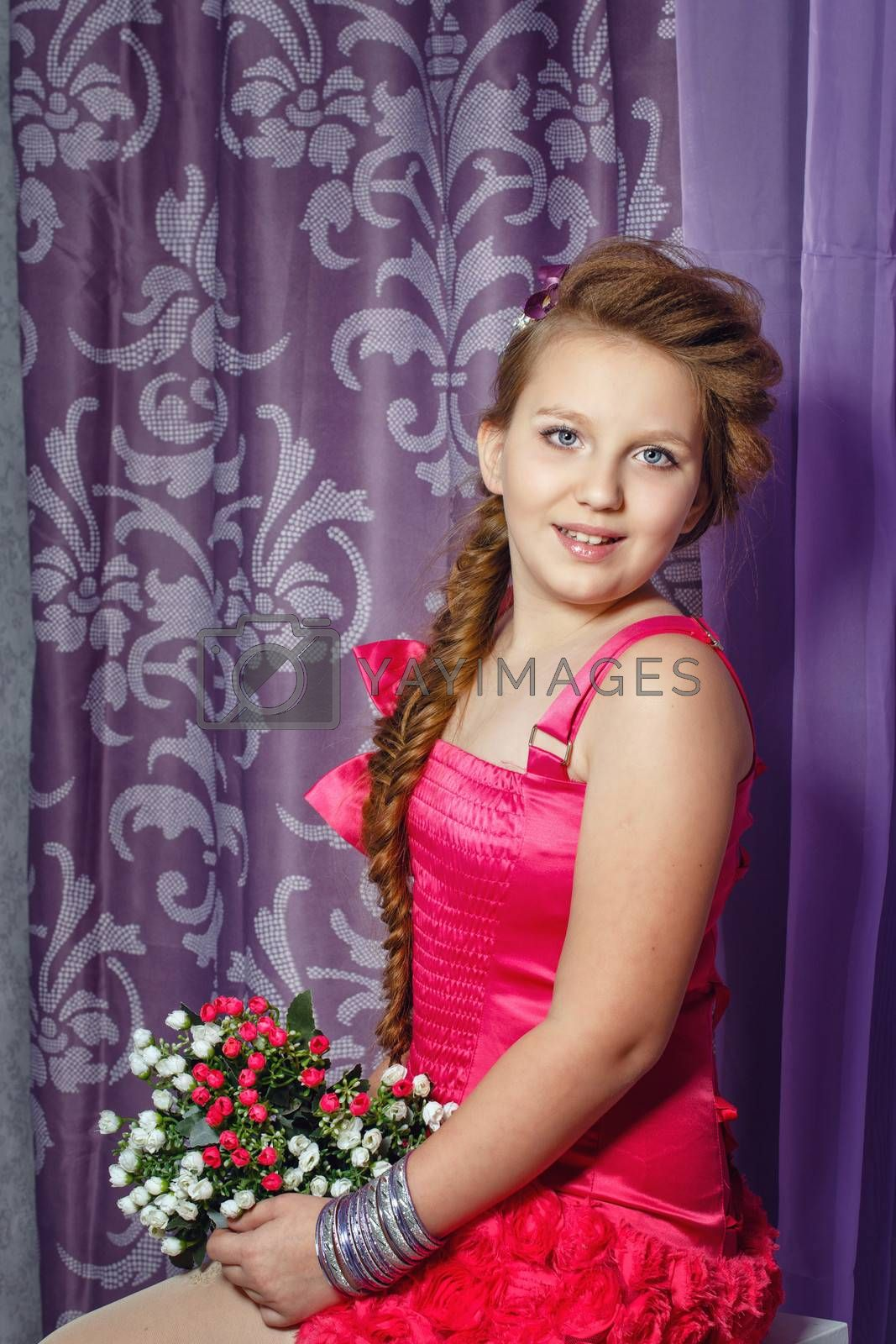Beautiful little girl in a pink dress with a bouquet of flowers posing in the interior