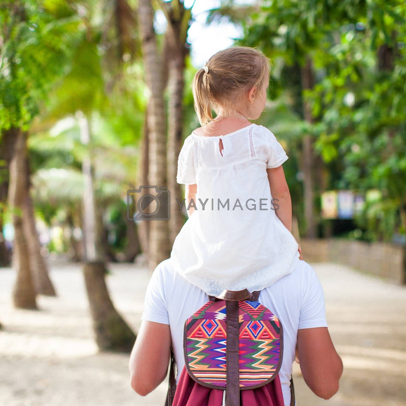 Little girl riding on her dad walking in the jungle
