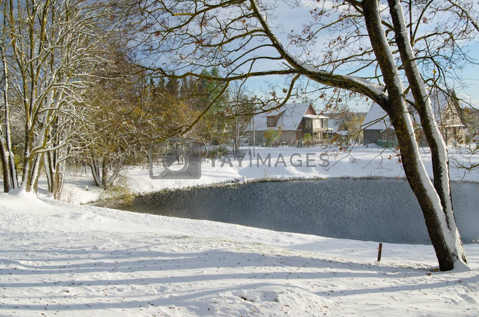 Autumn landscape with snow by a pond in rural