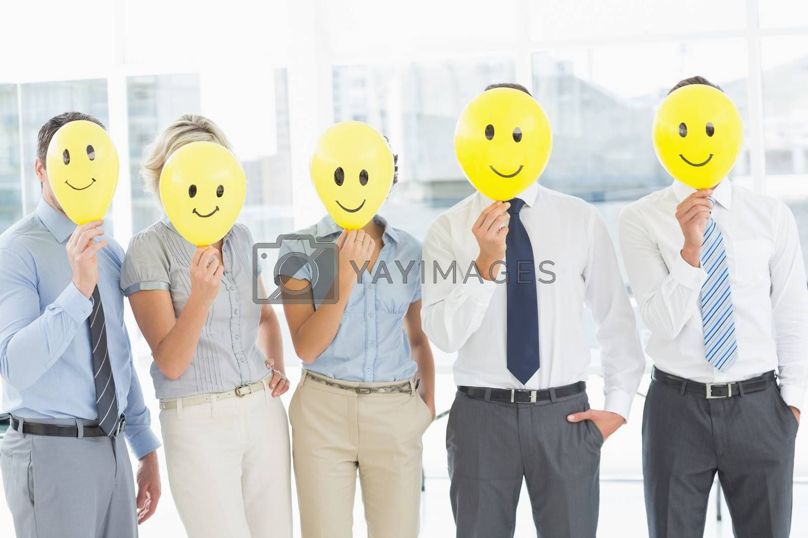 Group of business people holding happy smiles in front of their faces in a bright office