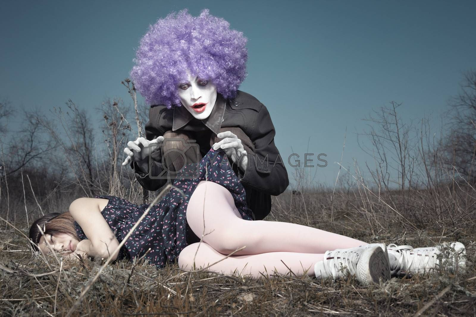 Sleeping girl outdoors and crazy maniac clown touching her shirt. Artistic colors added