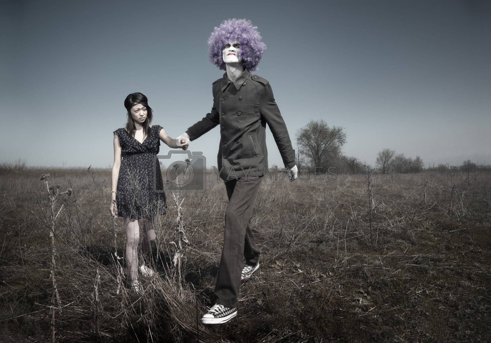 Bizarre couple in relationship conflict. Crazy clown and little girl outdoors. Natural lights and colors