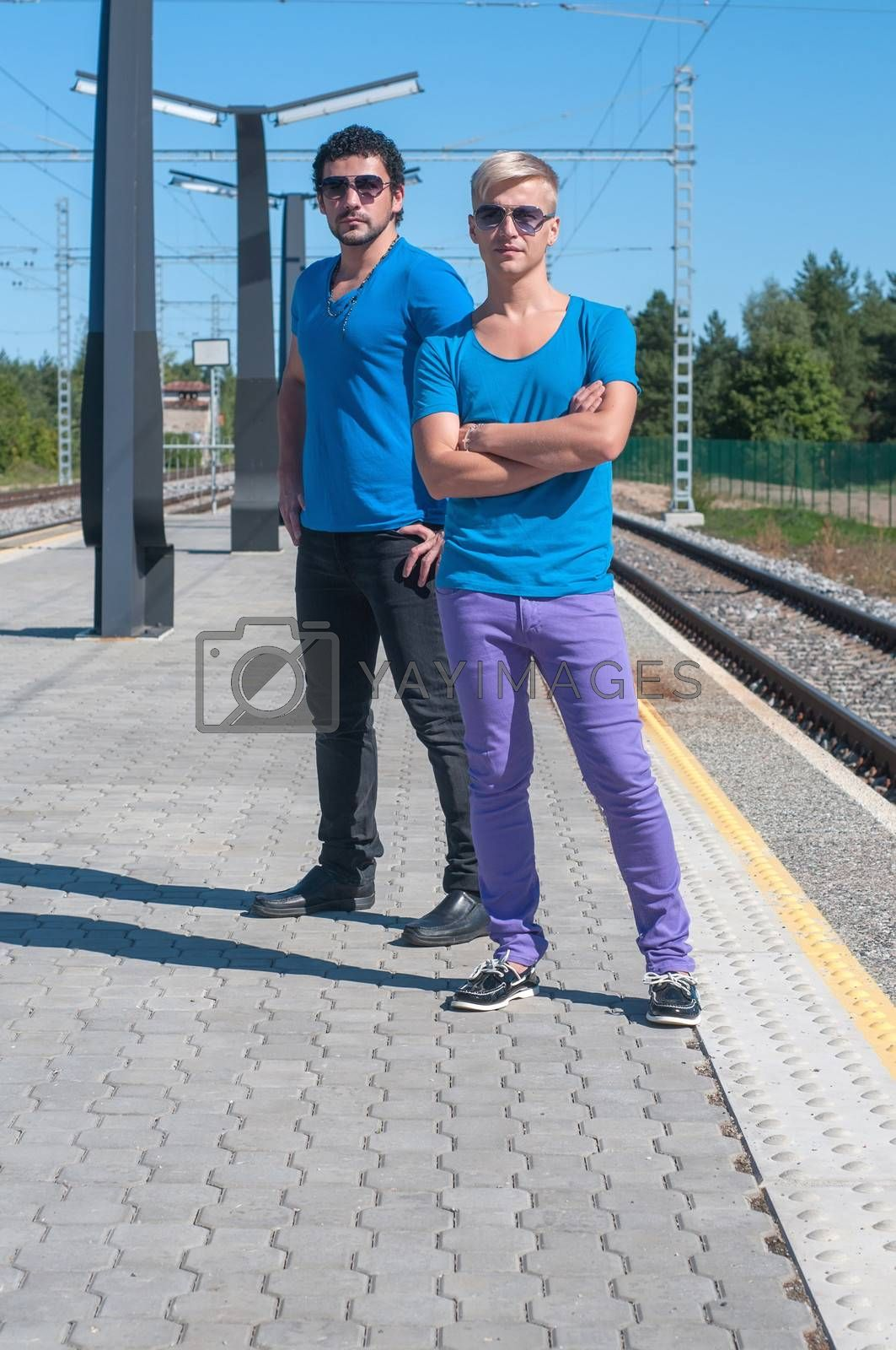 Shot of two young men standing on platform