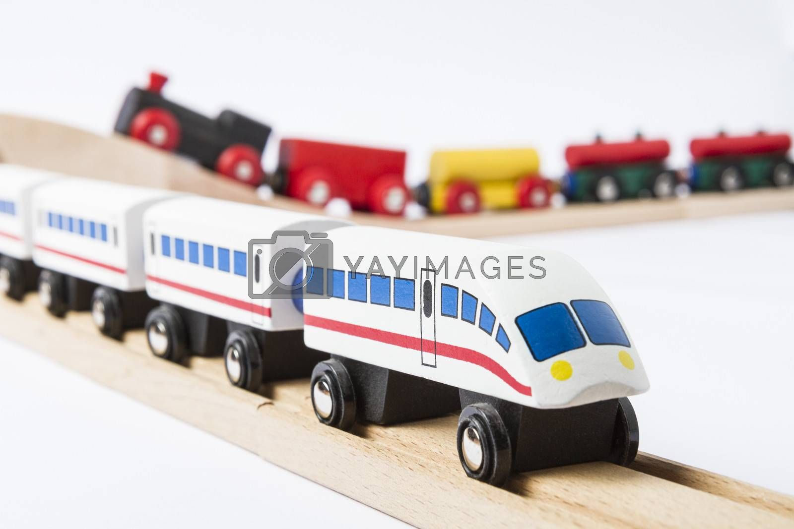 two wooden toy trains on railway isolated on white background