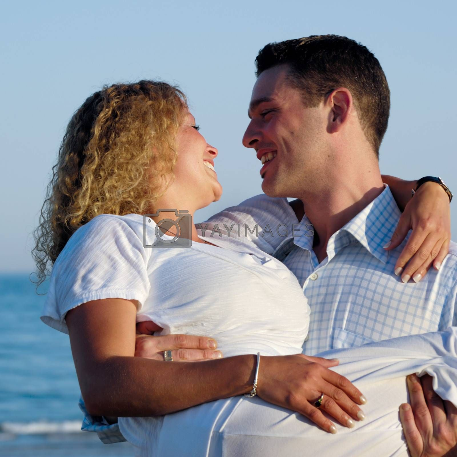 A happy woman and man in love at beach. The the young man is lifting his girlfriend.