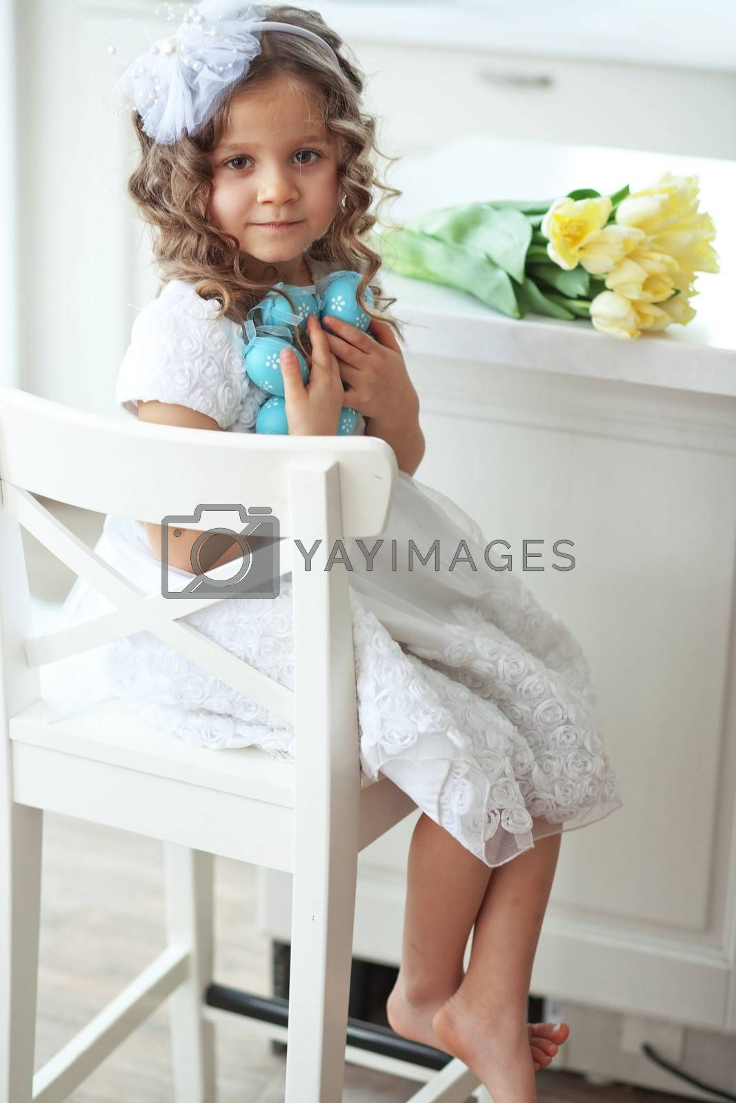 Beautiful little child wearing flower girl dress posing with the Easter eggs and bouquet of spring tulips