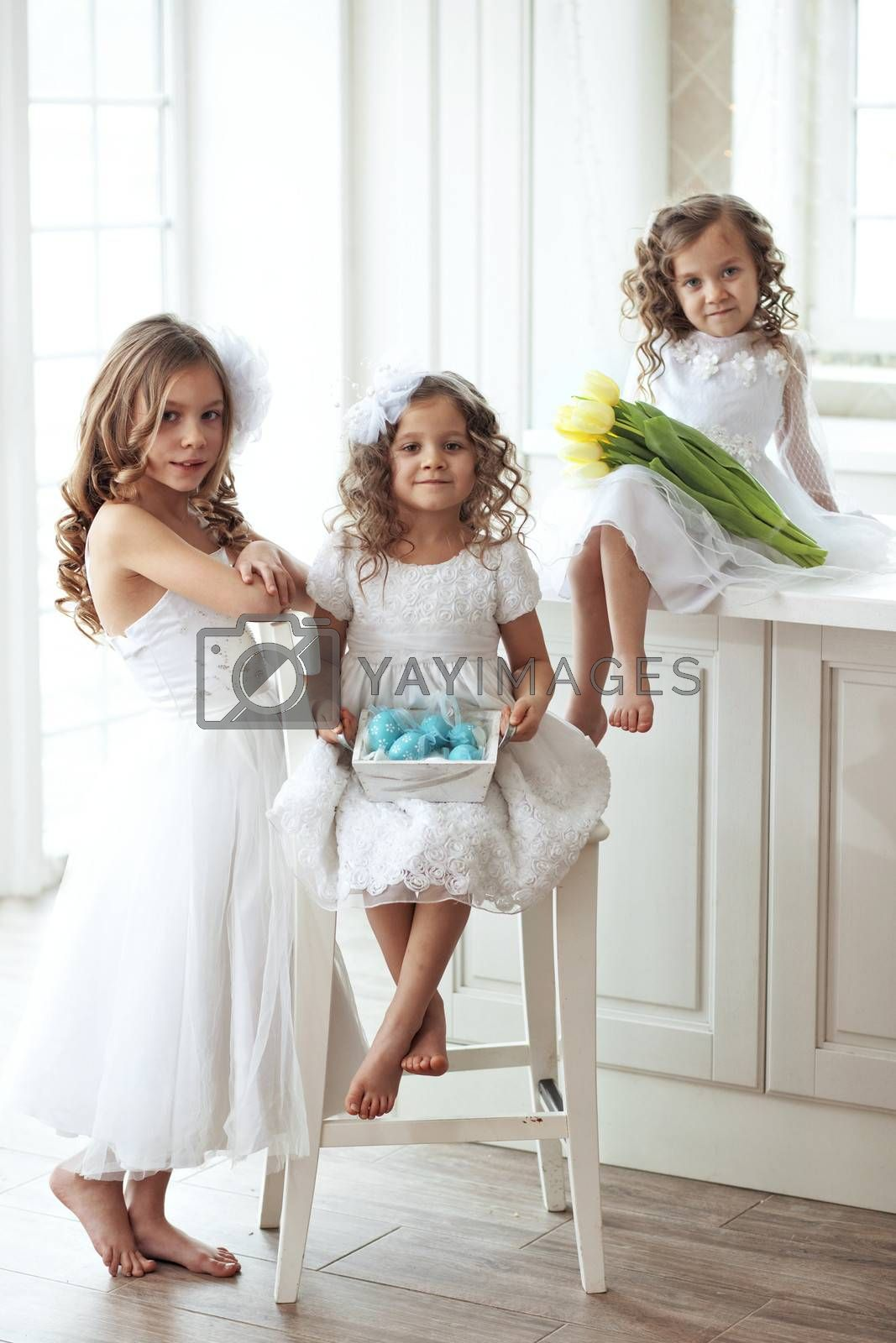 Beautiful little children wearing flower girl dresses posing with the Easter eggs and bouquet of spring tulips