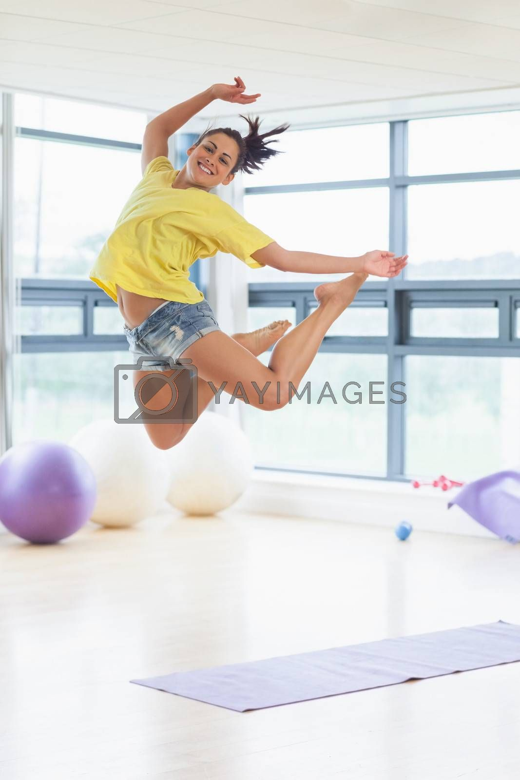 Full length portrait of young woman jumping in fitness studio