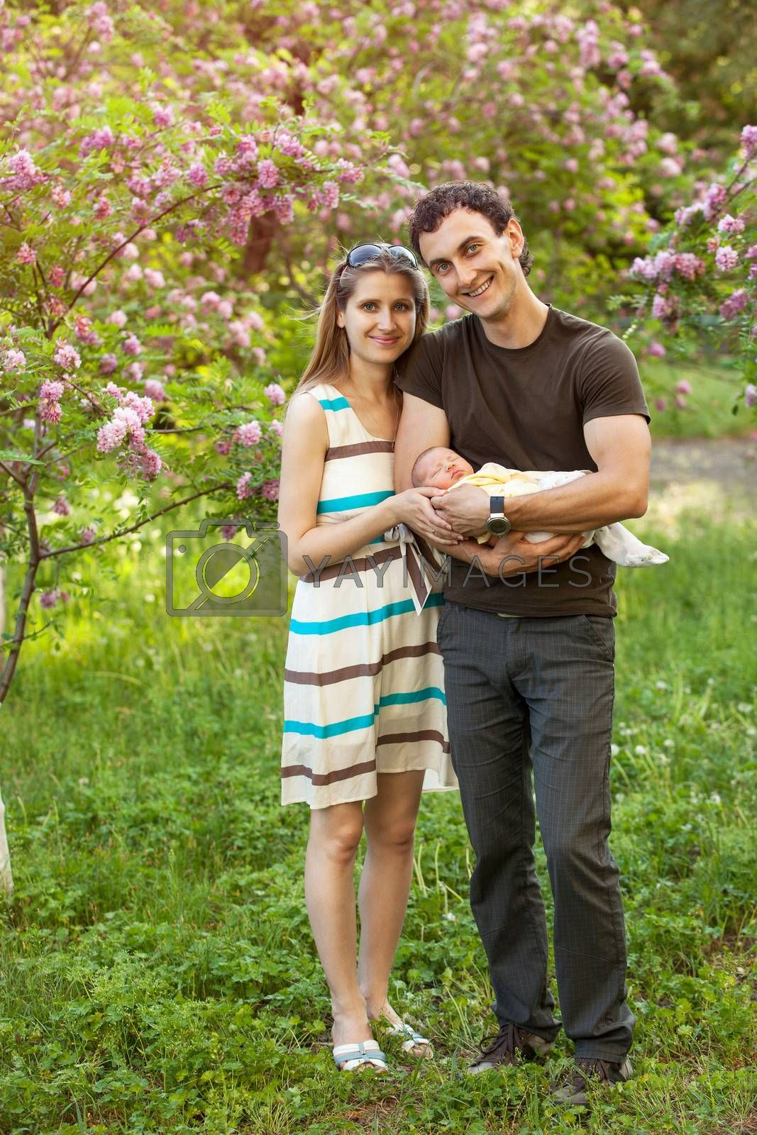 Happy young couple with newborn son outdoors in spring