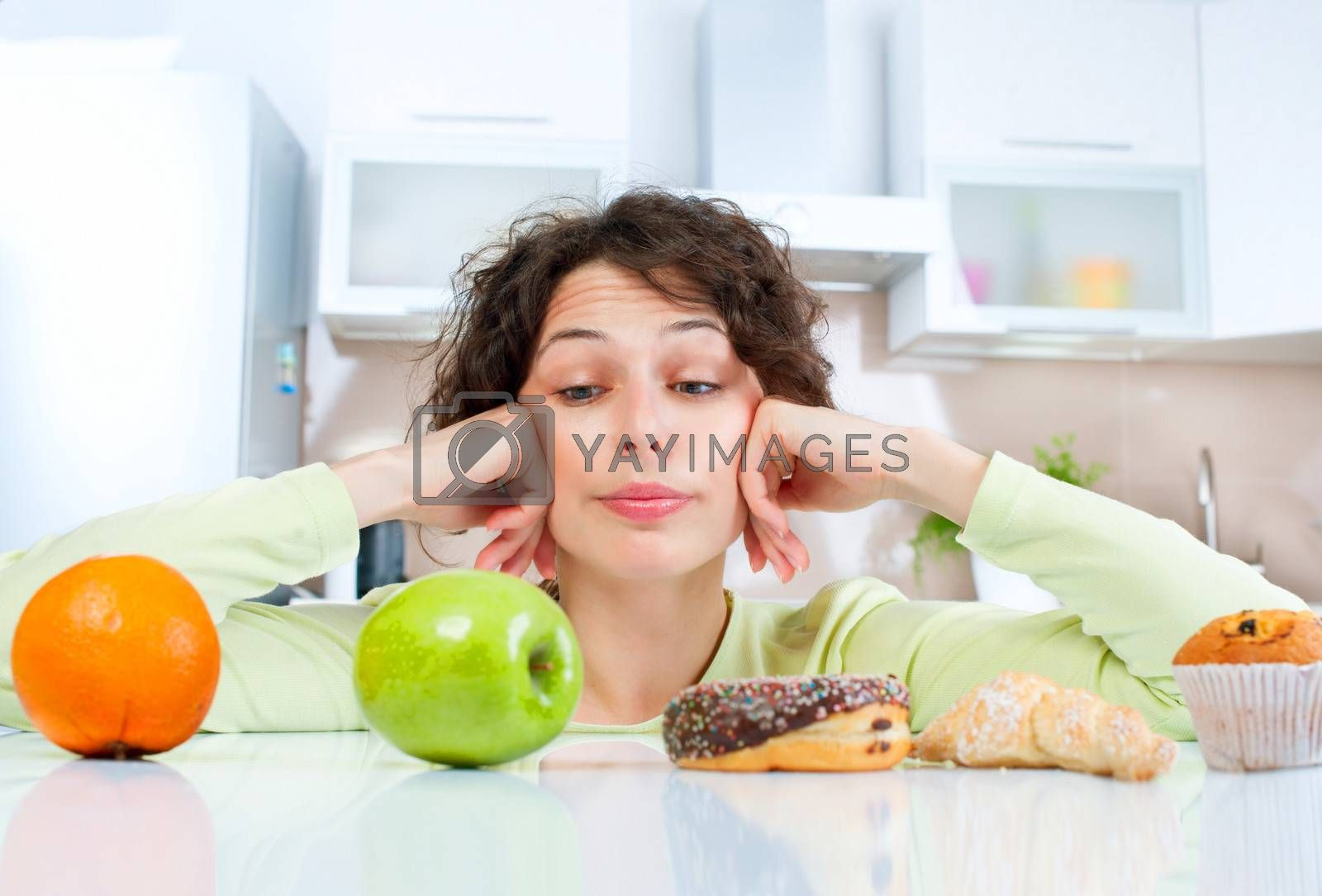 Dieting concept. Young Woman choosing between Fruits and Sweets by SubbotinaA
