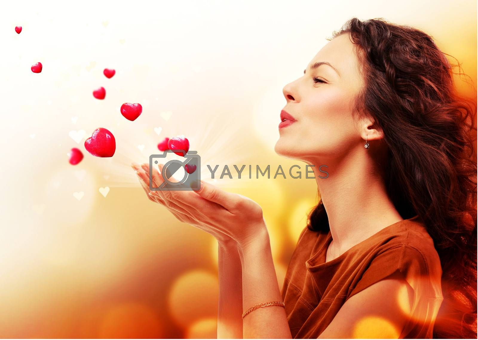 Woman Blowing Hearts from her Hands. St. Valentines Day Concept