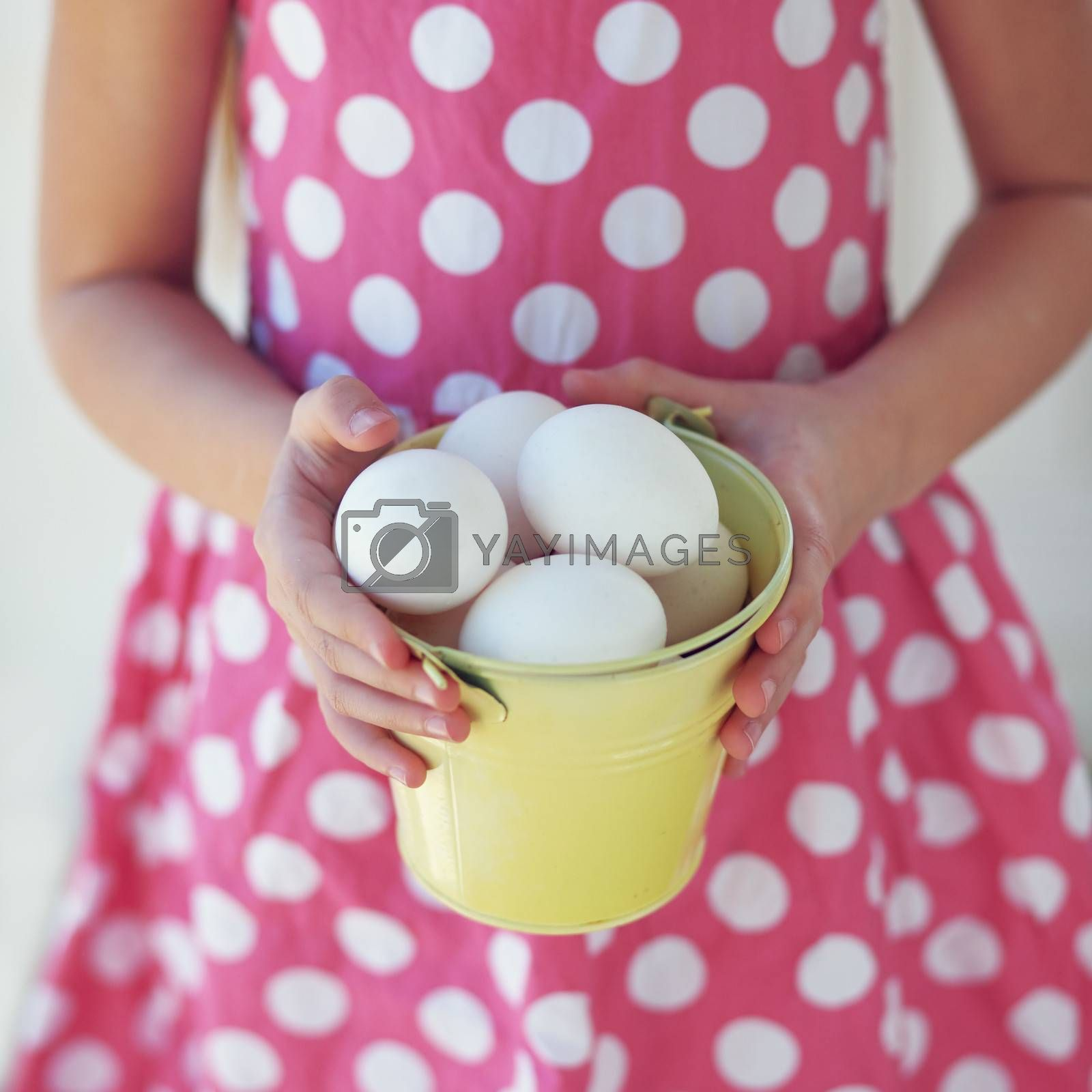Portrait of kid's hands holding tin pot with Easter eggs closeup