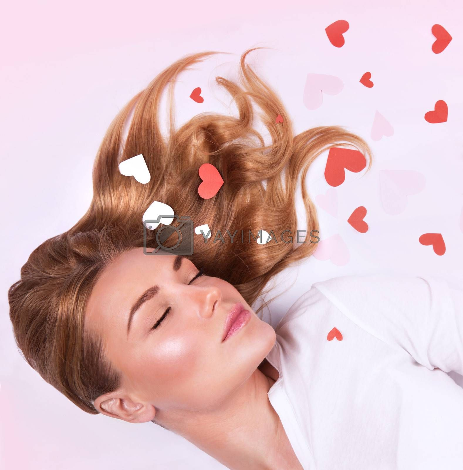 Closeup portrait of dreamy girl with closed eyes lying down on white background, red heart decoration, Valentines day, love and romance concept