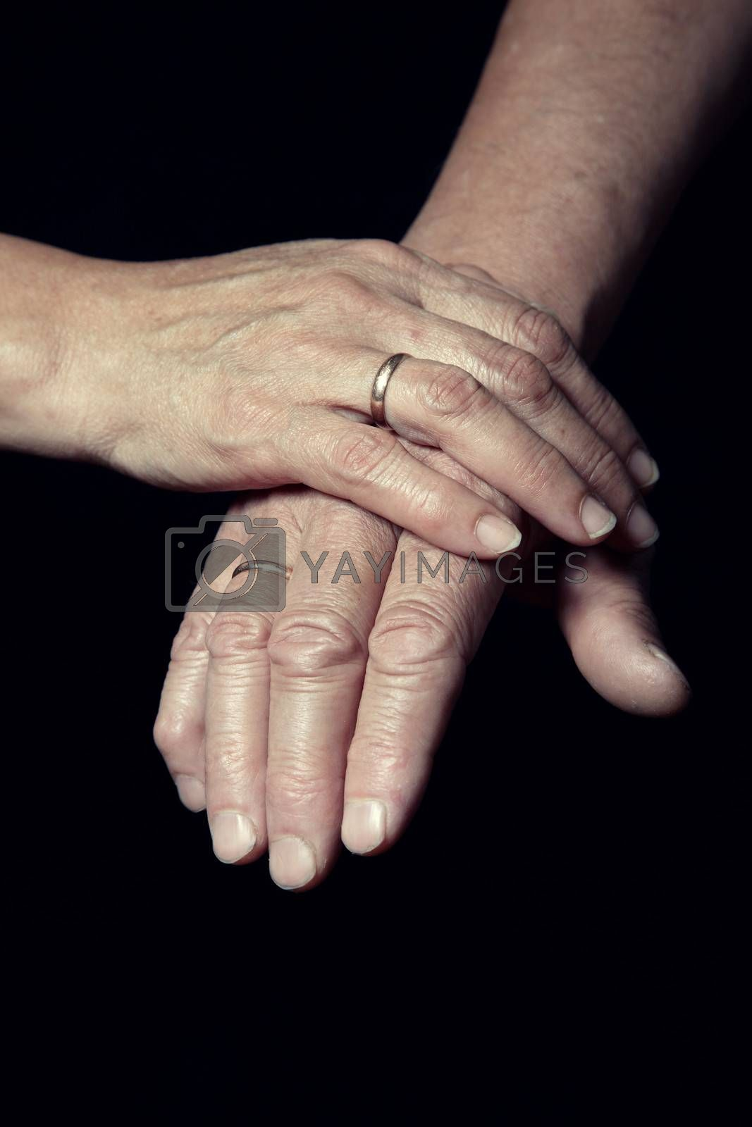 Hands of two loving senior people on a dark background