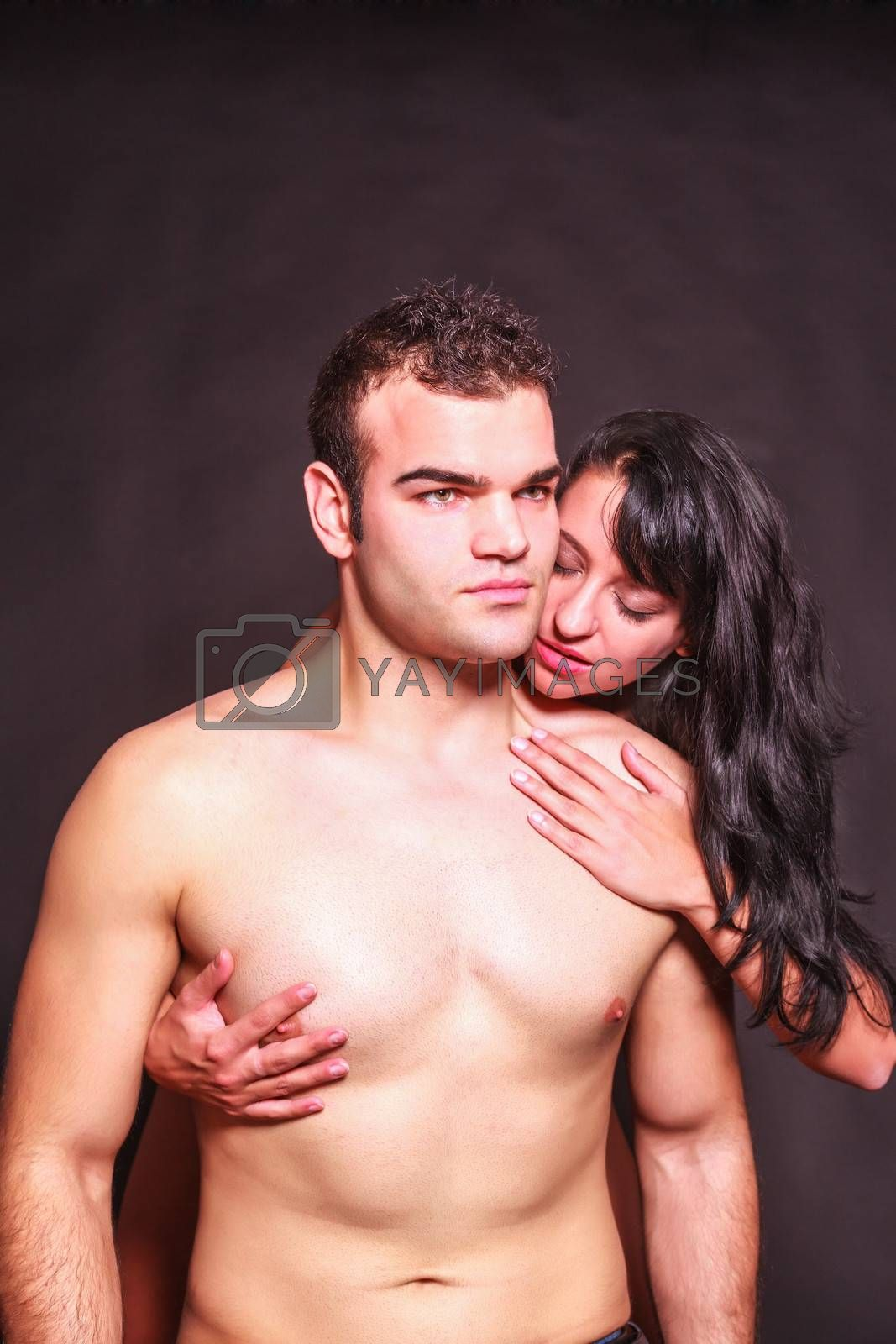 Seductive passionate woman running her hands over the naked body of a handsome young man as she nibbles at his neck from behind
