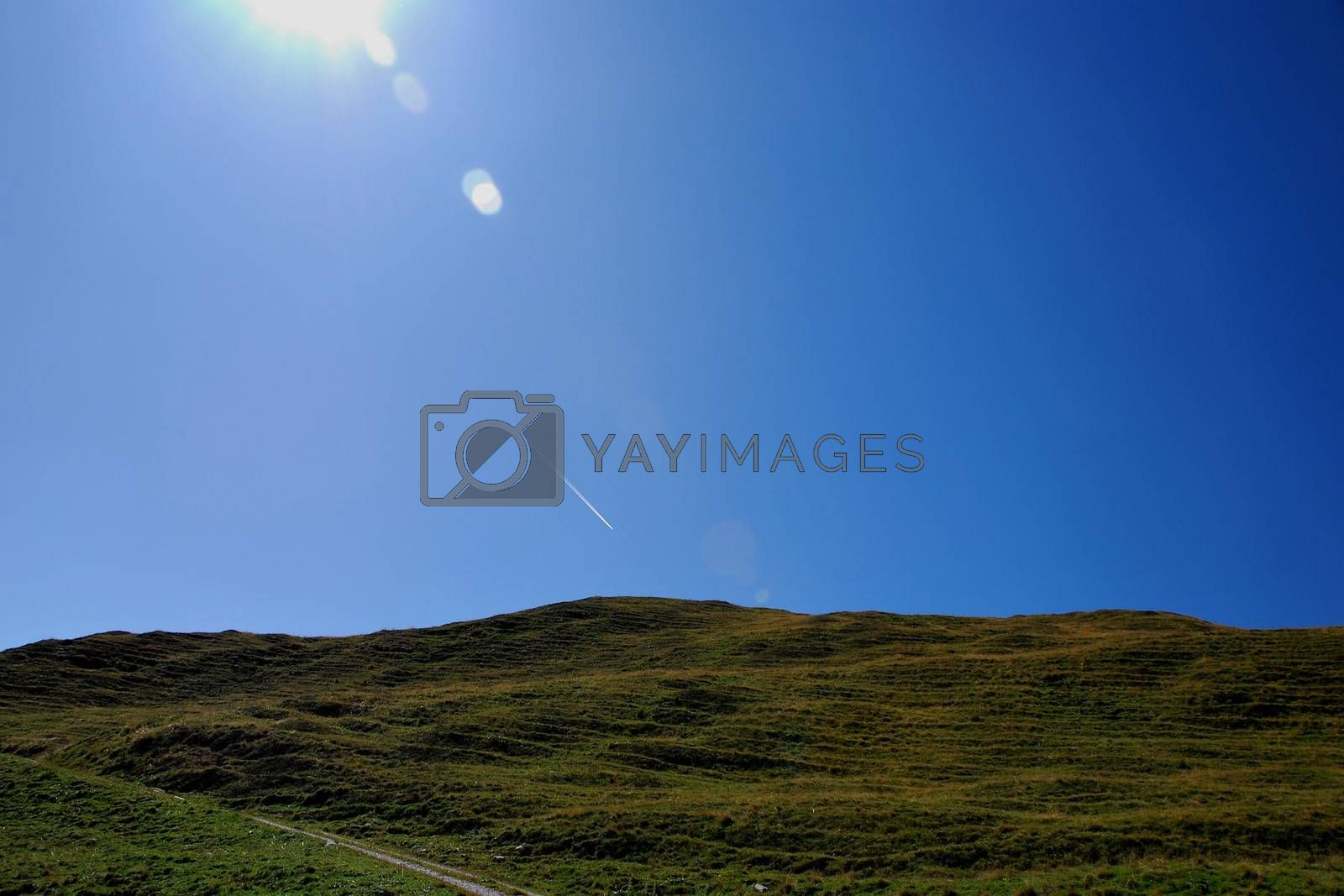 green hill with blue sky and sun rays