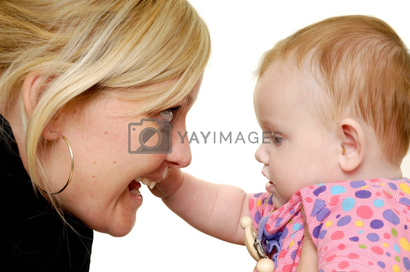 Mother is looking down on her sweet smiling baby. Taken on a white background.