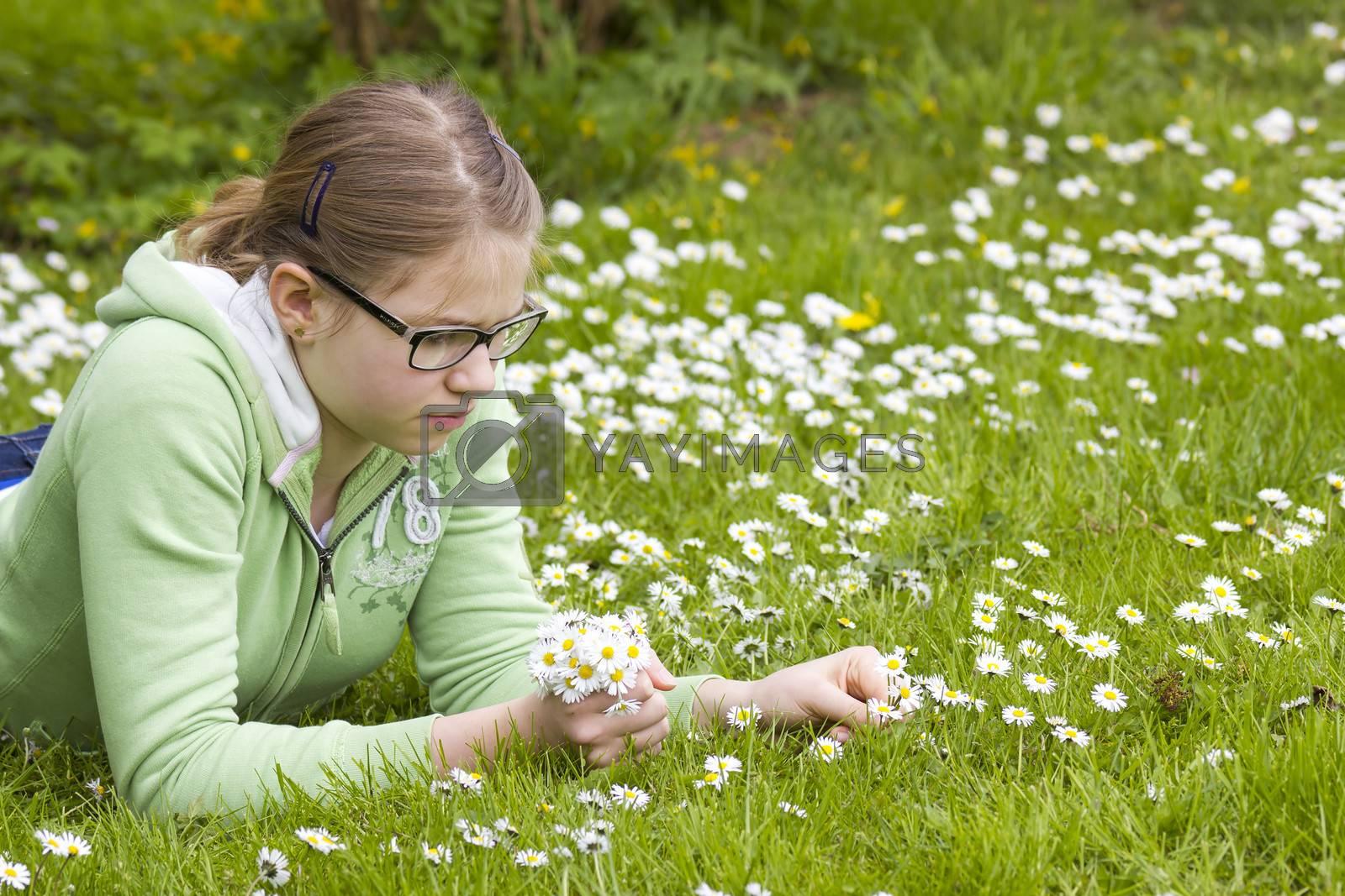 young girl picking daisies by miradrozdowski