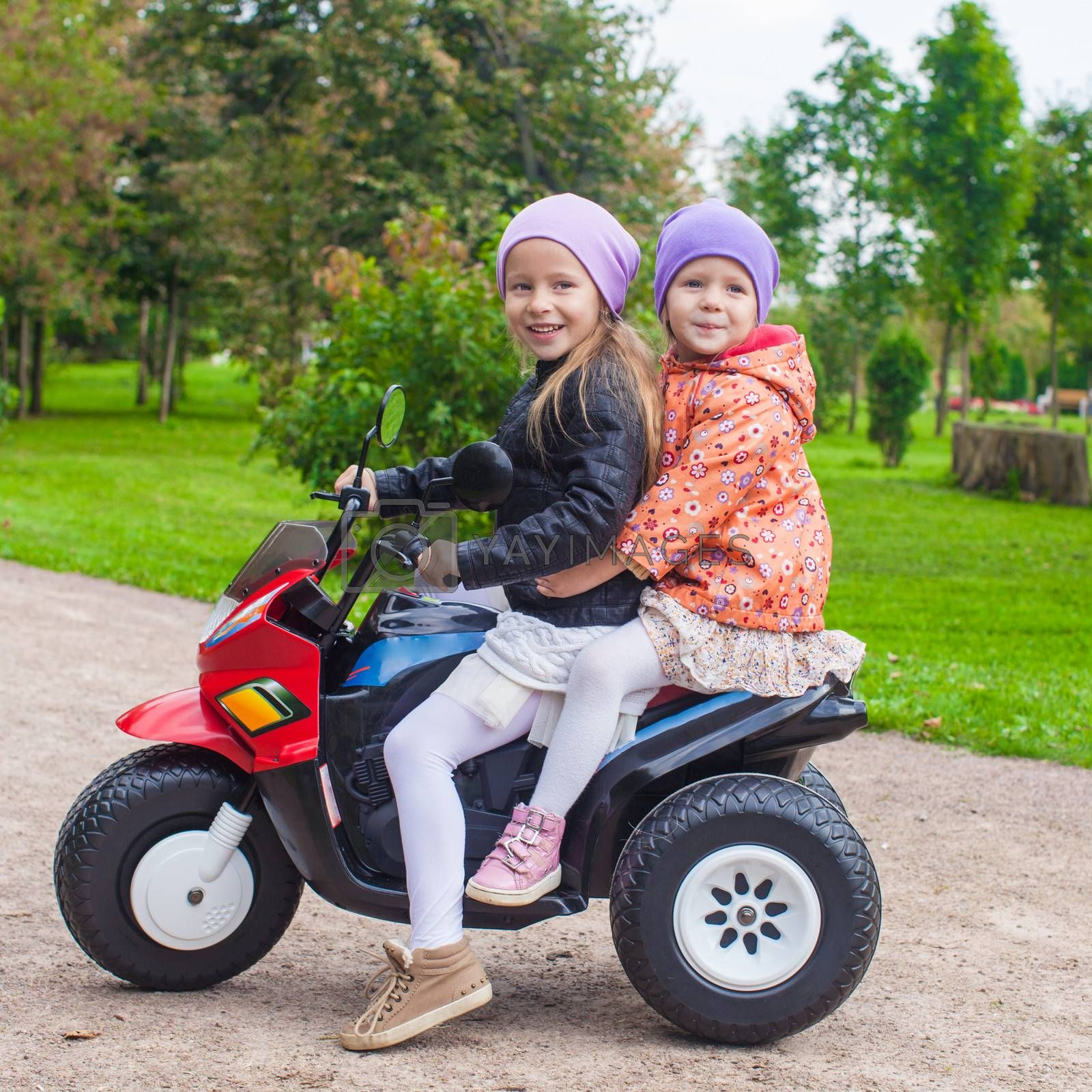 Two Little beautiful sisters sitting on toy motorcycle in green park