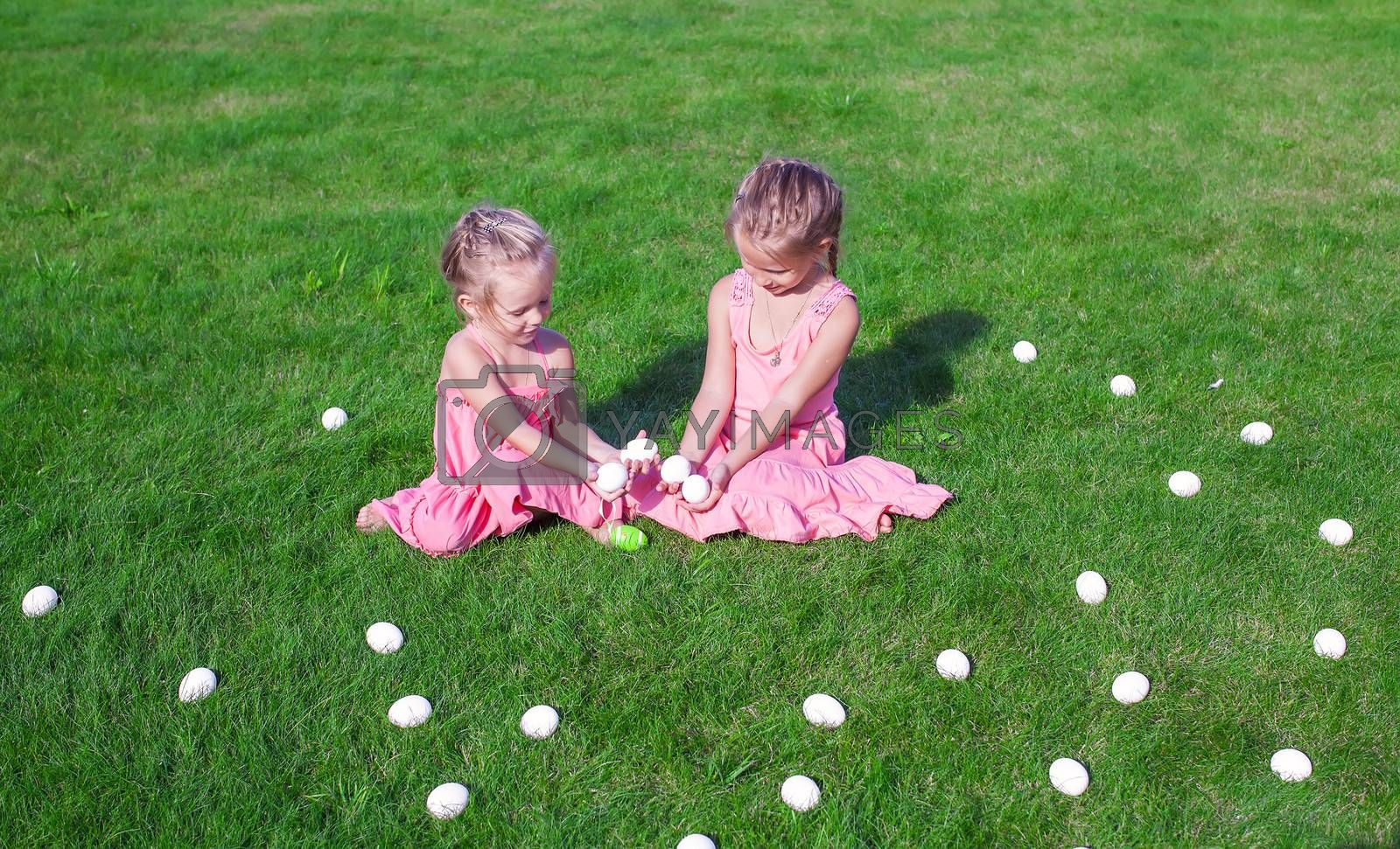 Two adorable little girls playing with Easter Eggs in the yard