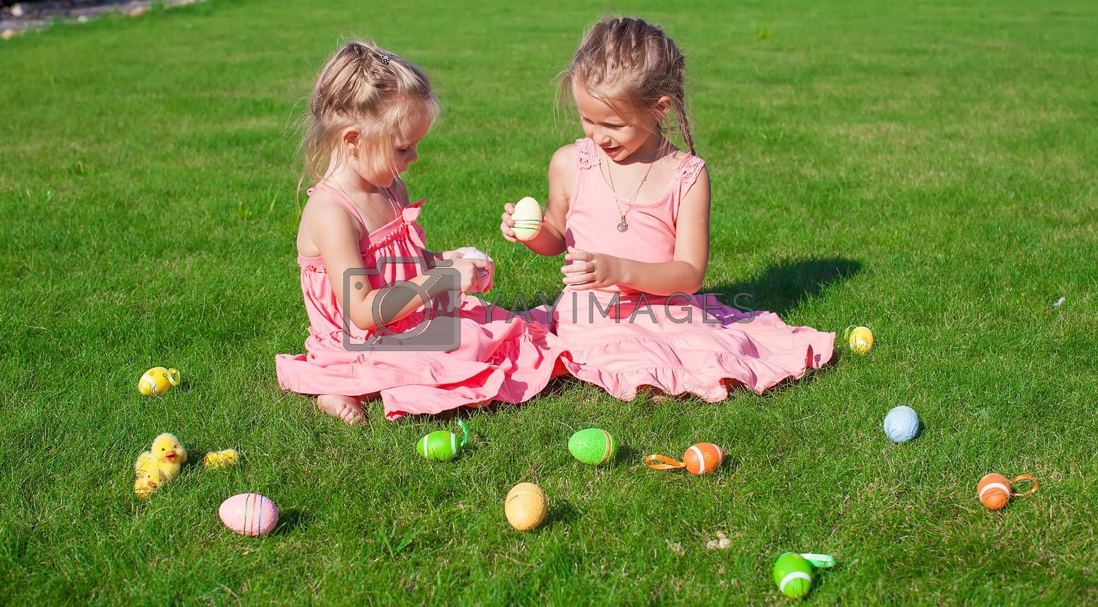 Royalty free image of Two adorable little sisters playing with Easter Eggs by travnikovstudio