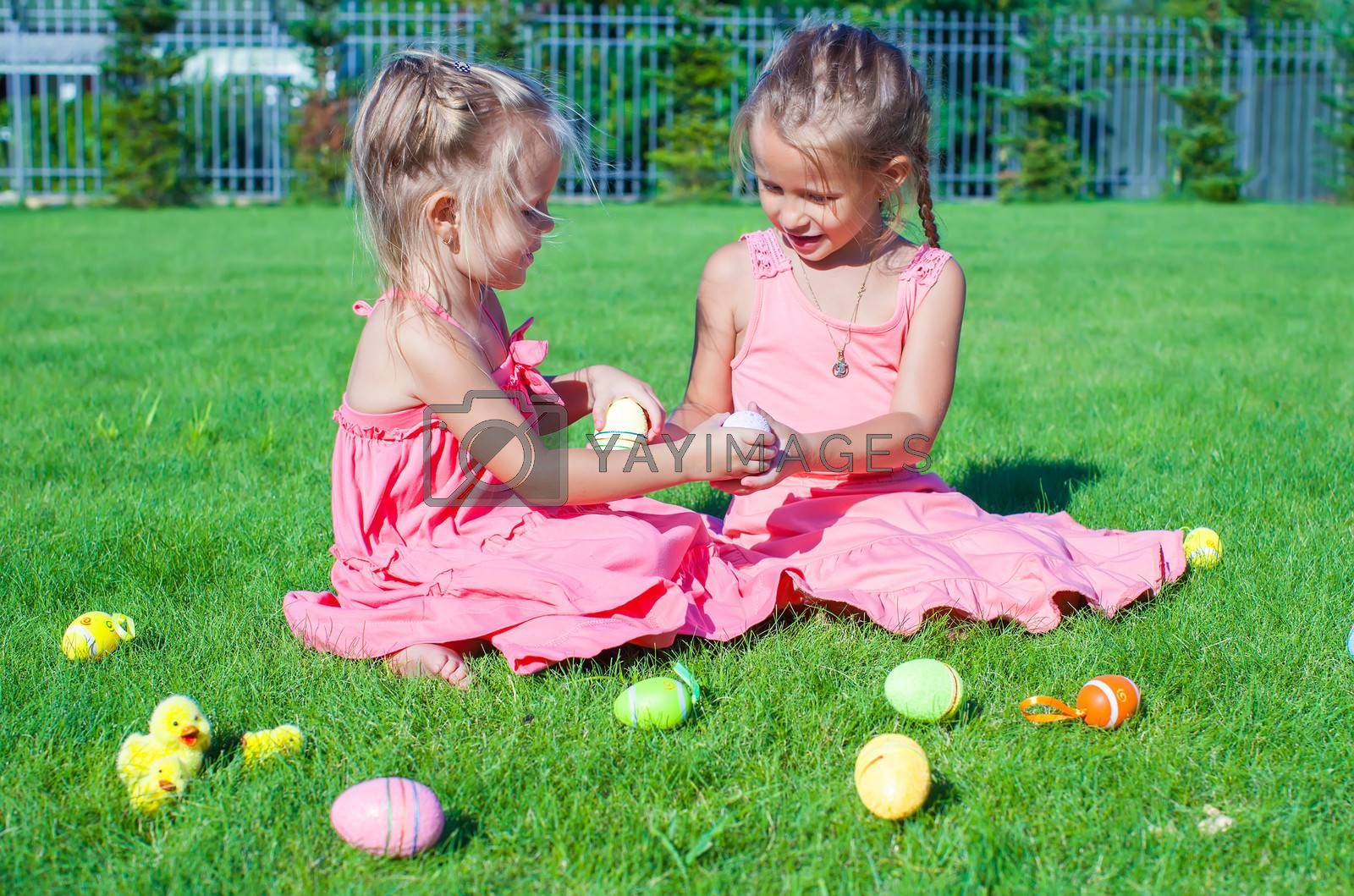 Adorable little girls playing with Easter Eggs on green grass
