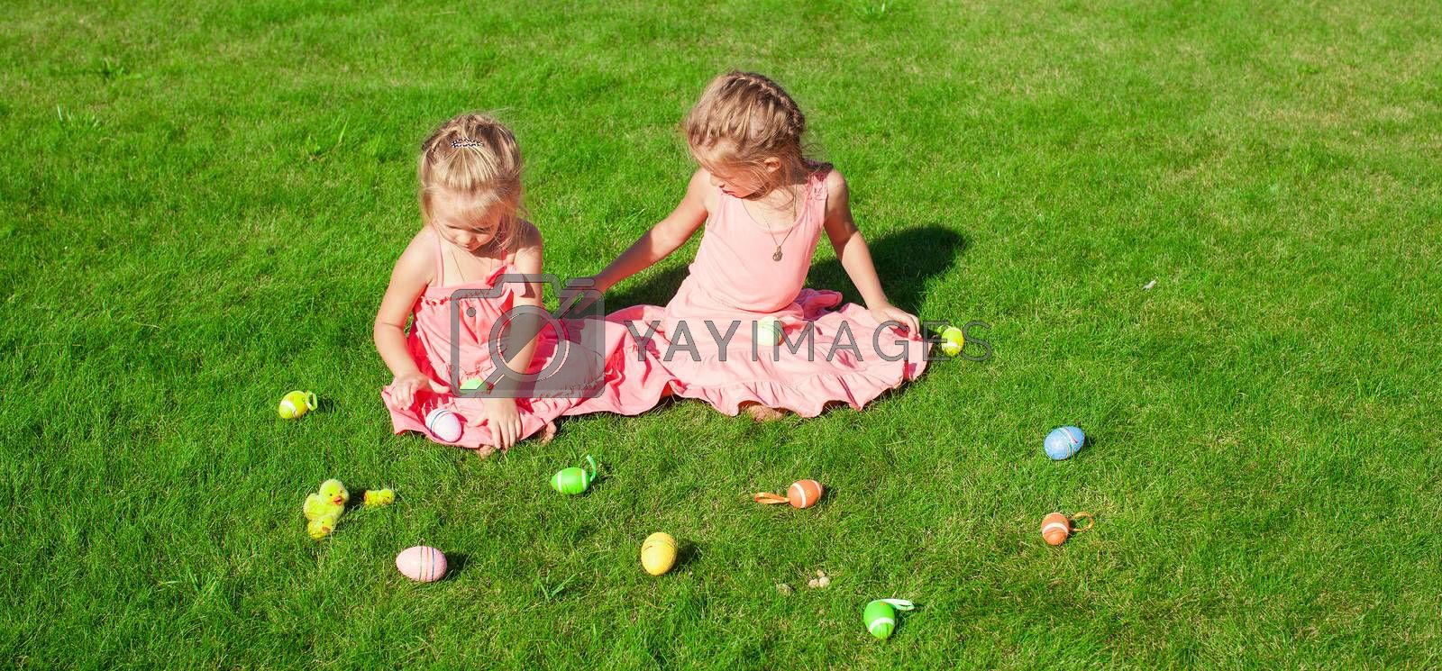 Two adorable little girls playing with Easter Eggs