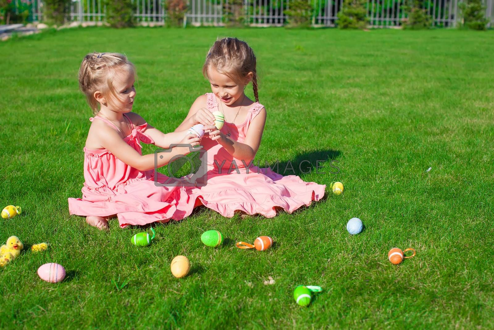 Two adorable little sisters playing with Easter Eggs
