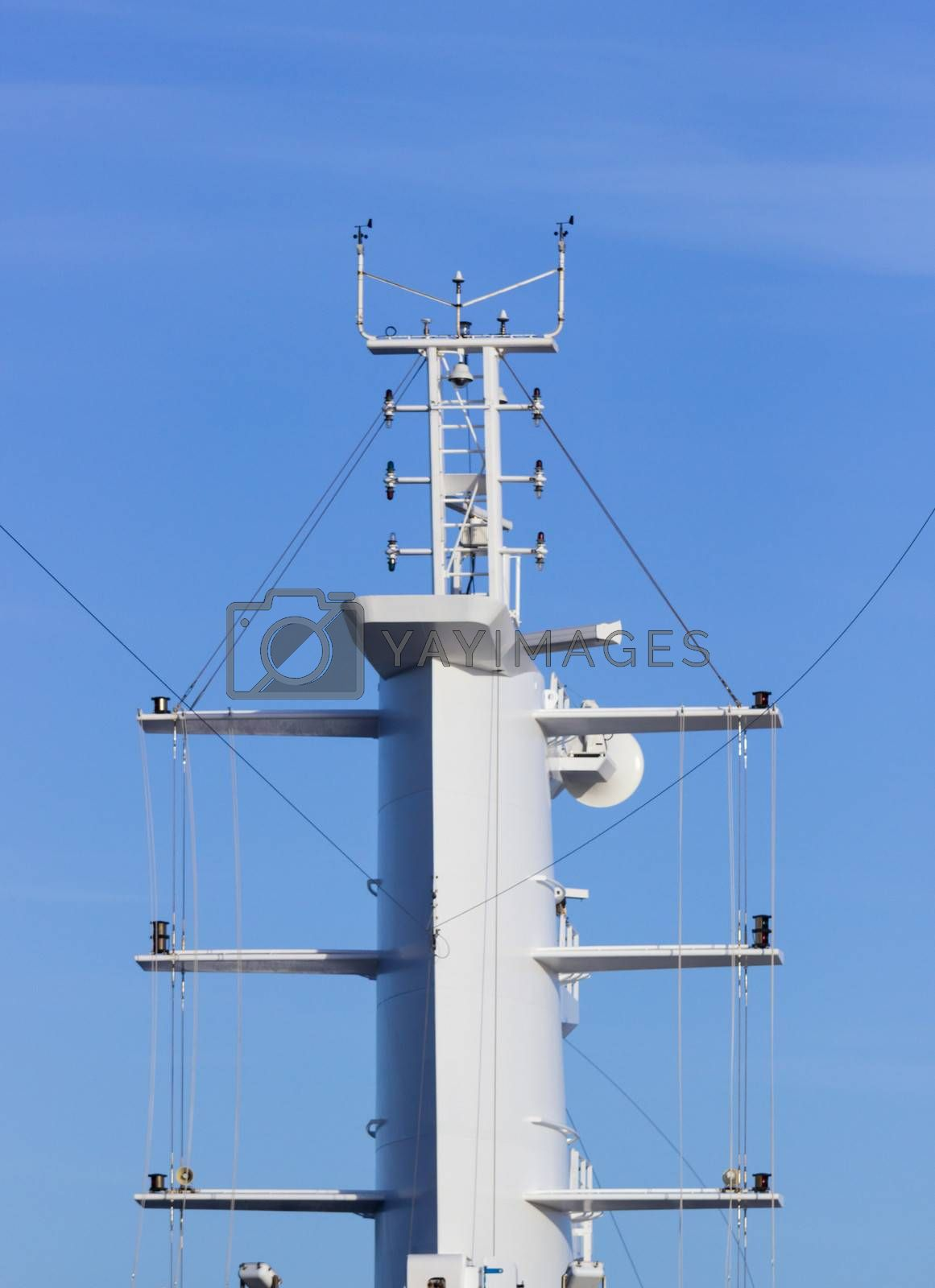 Communication tower or mast on large cruise ship with aerials and antennae against blue sky