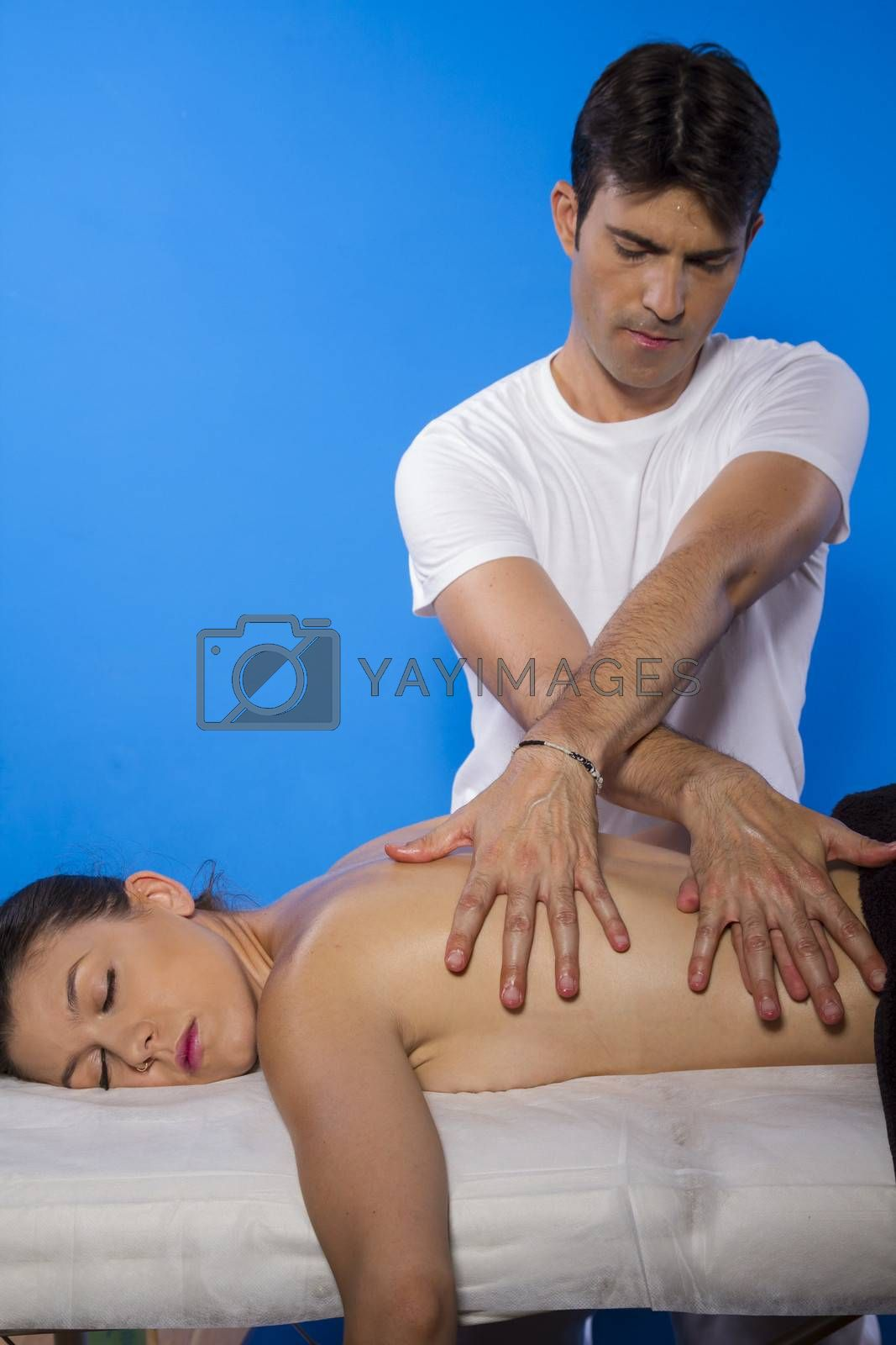 Lying.masseur doing massage on woman body in the spa salon. Beauty treatment concept.