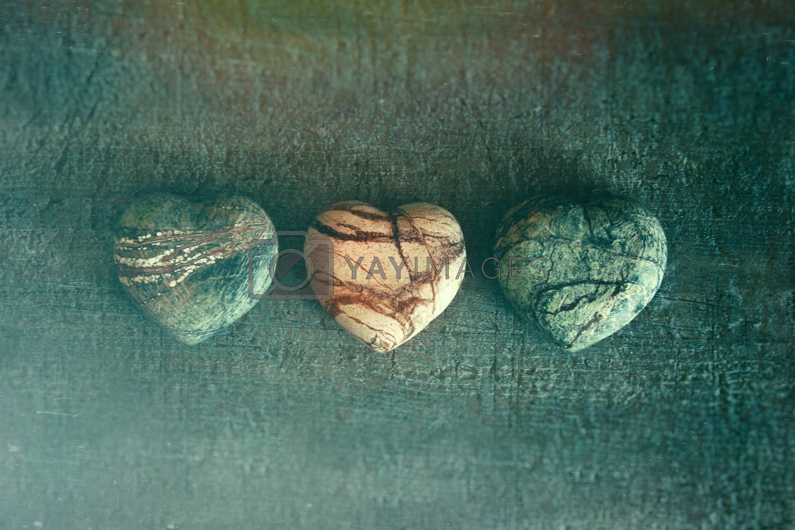 Three stone hearts on wood background