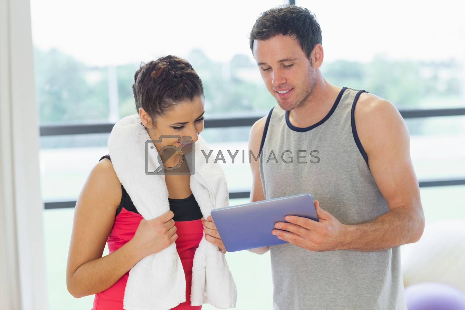 Fit young couple looking at digital table in a bright exercise room
