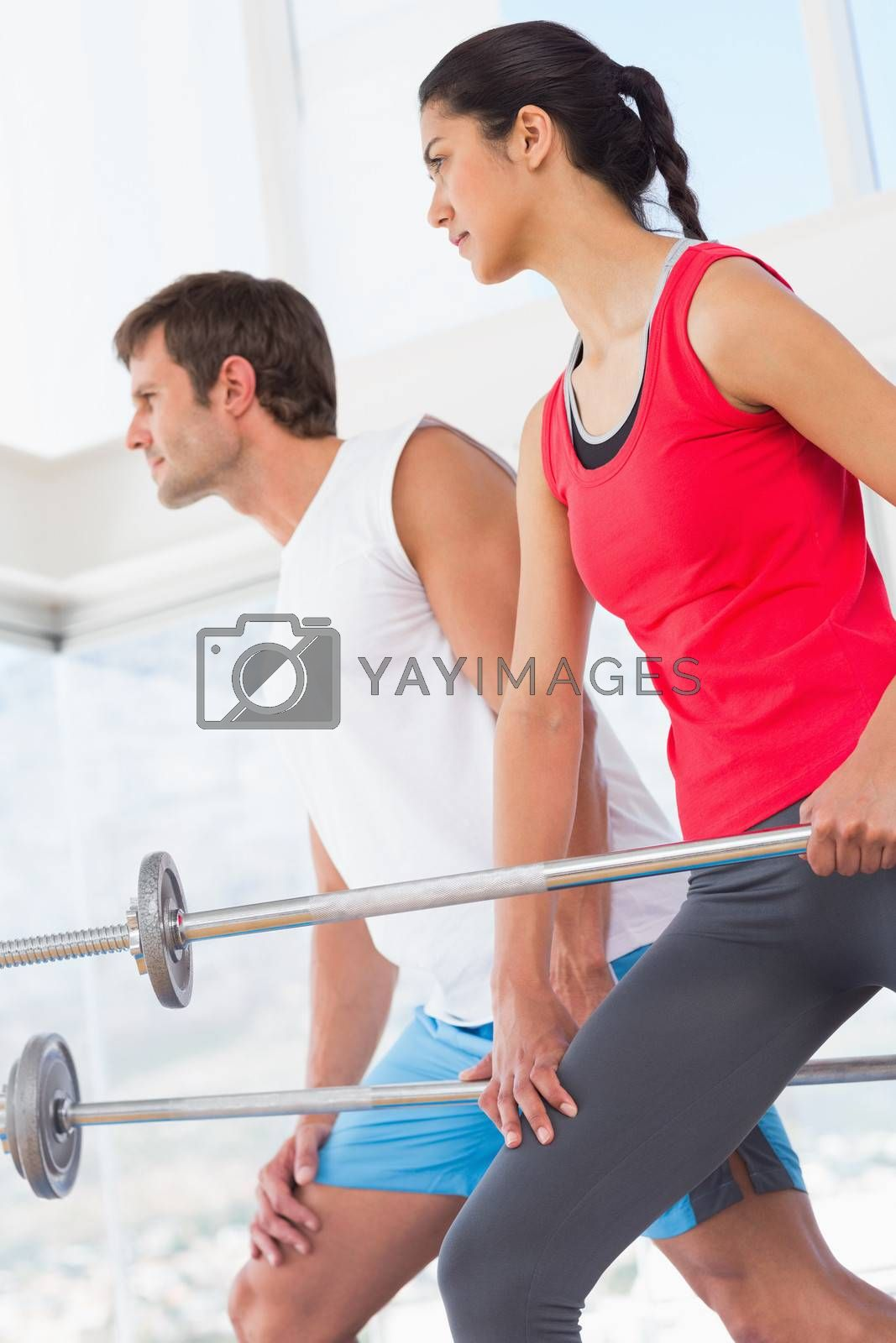 Side view of fit young man and woman holding barbells in the gym