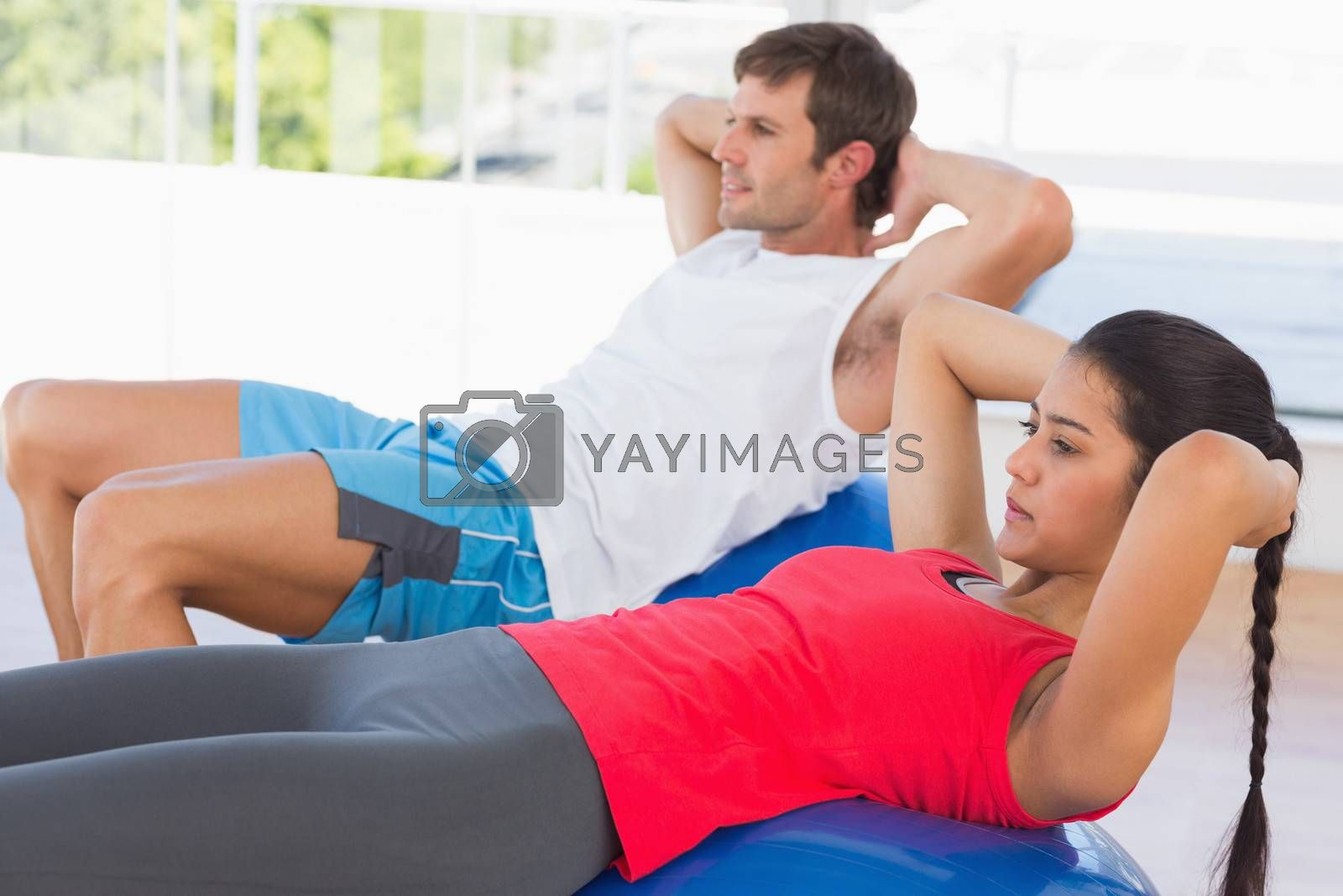 Side view of a fit young couple exercising on fitness balls in the bright gym