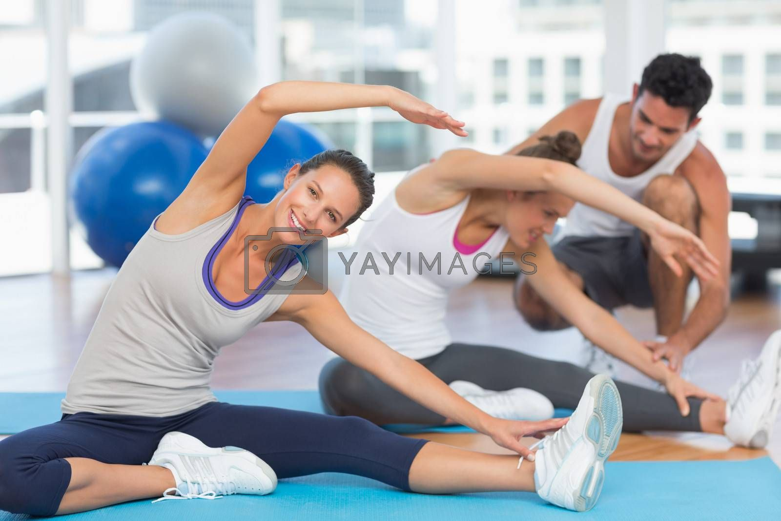 Women doing stretching exercises as trainer helps one at fitness studio