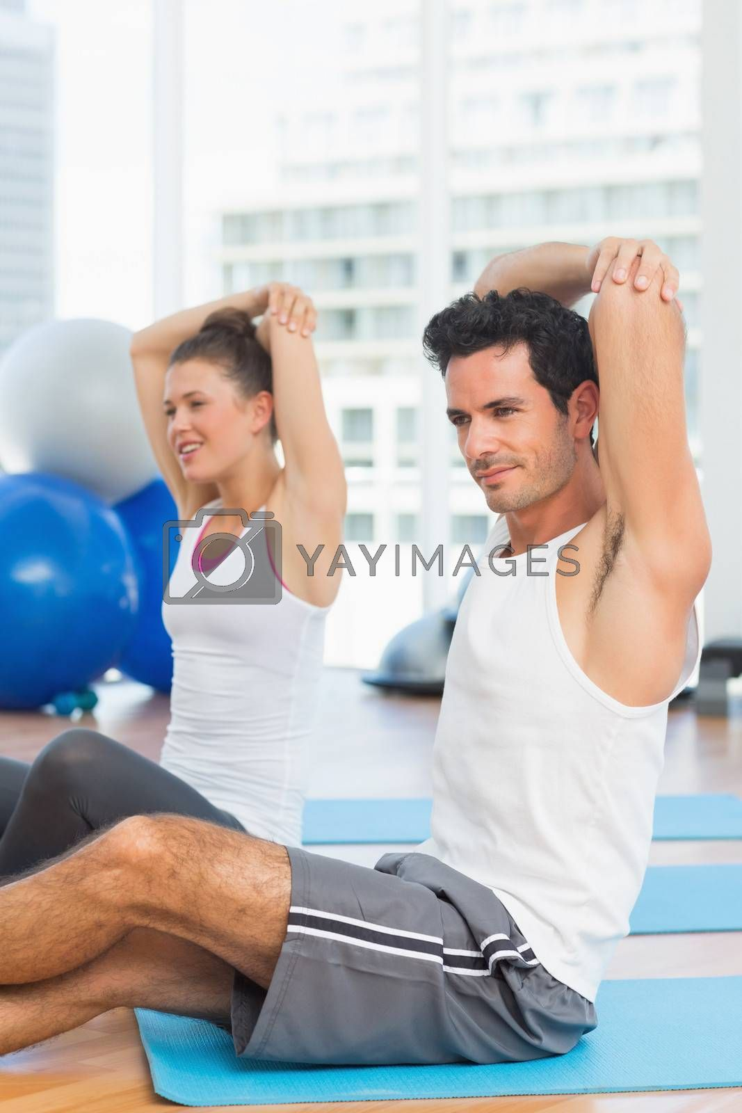 Two sporty people stretching hands at yoga class in fitness studio