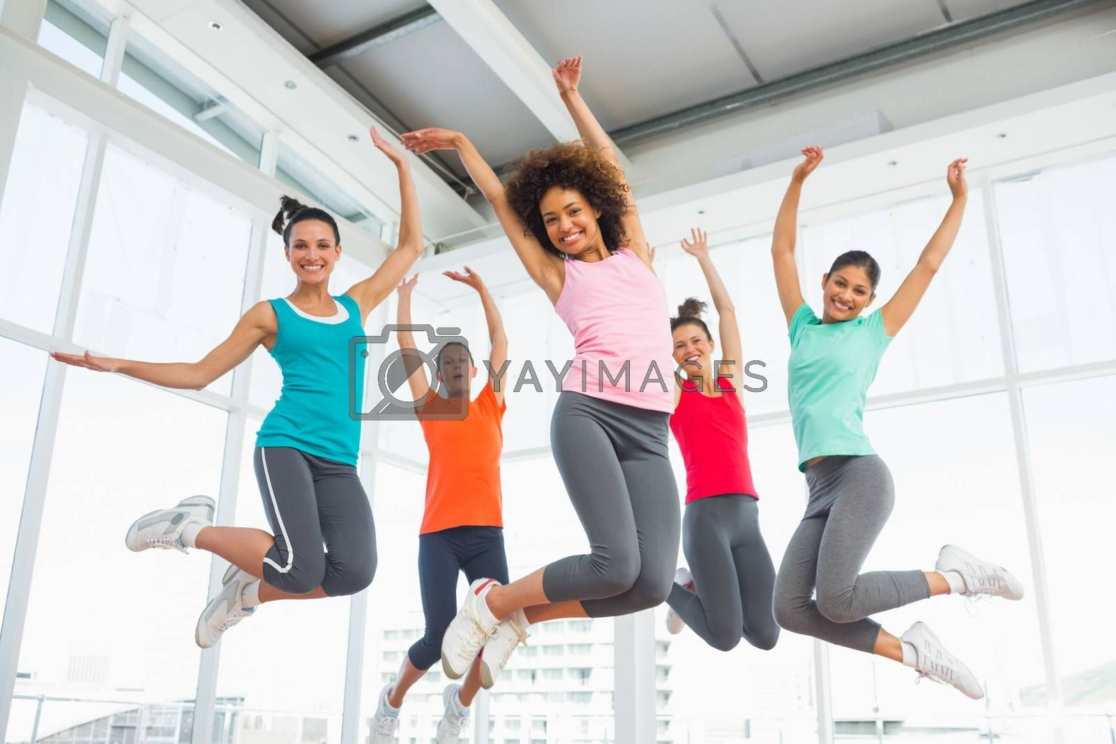 Full length portrait of fitness class and instructor jumping in fitness studio