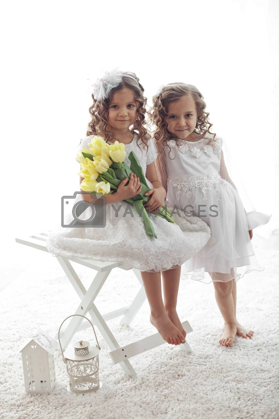 Beautiful little children wearing flower girl dresses posing with the bouquet of spring tulips