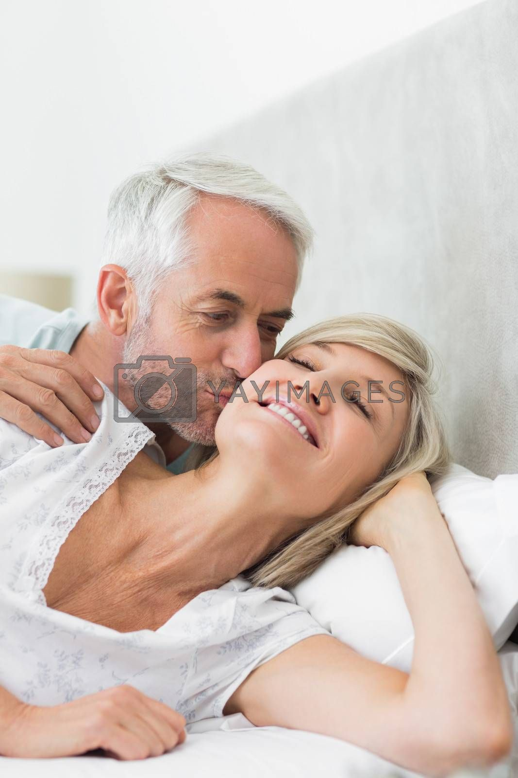 Closeup of a mature man kissing womans cheek in bed at the home