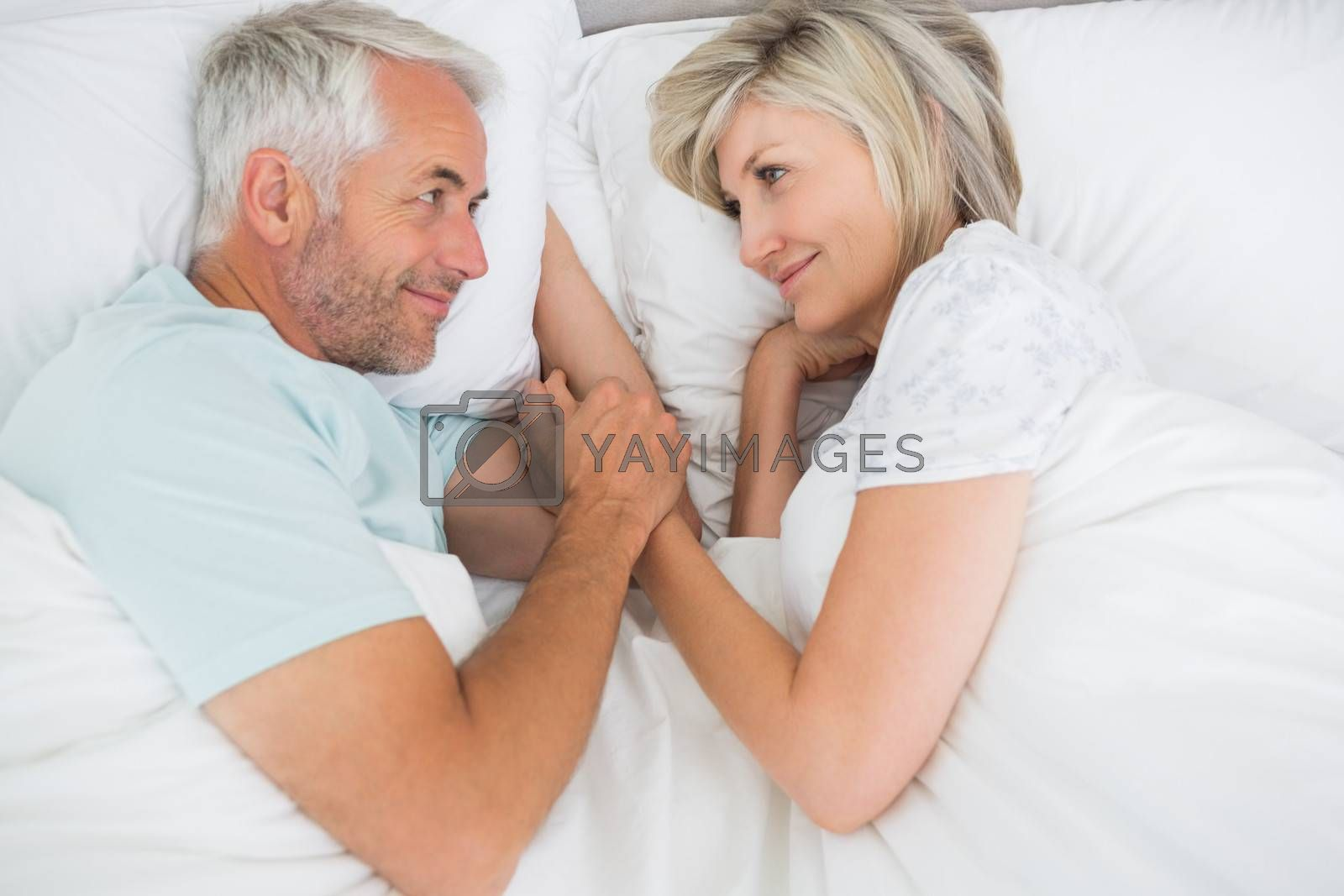 Loving mature man and woman lying in bed at the home