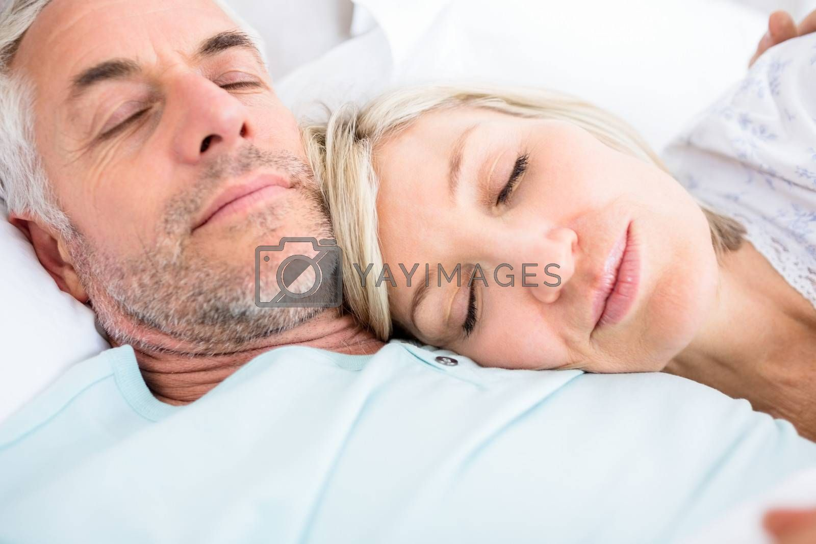 Closeup of a loving mature couple sleeping in bed at home
