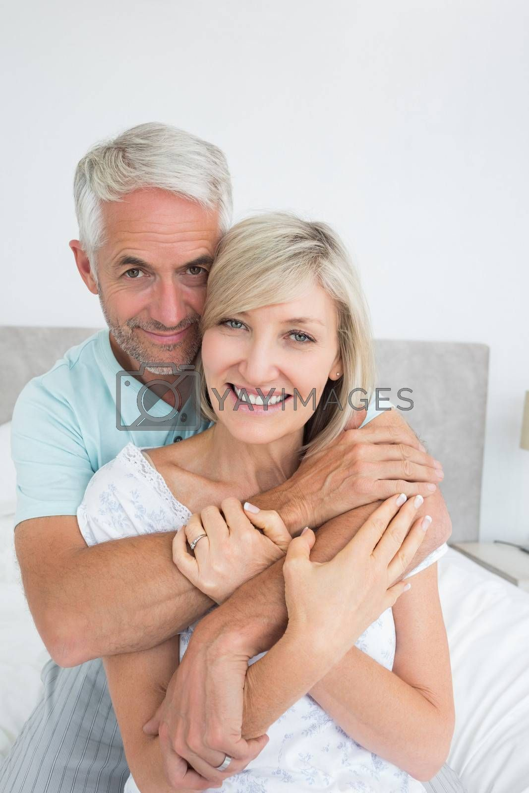 Closeup portrait of a loving mature man embracing woman in bed at home