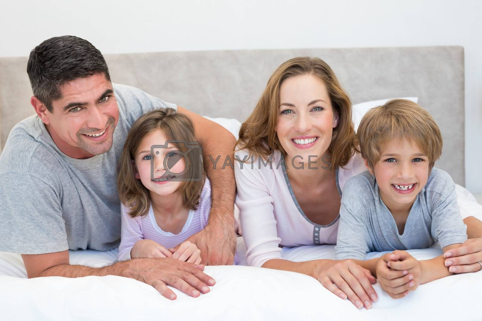 Portrait of smiling family lying side by side in bed