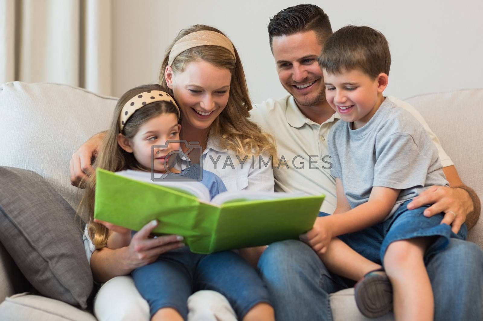 Family watching photo album on sofa by Wavebreakmedia