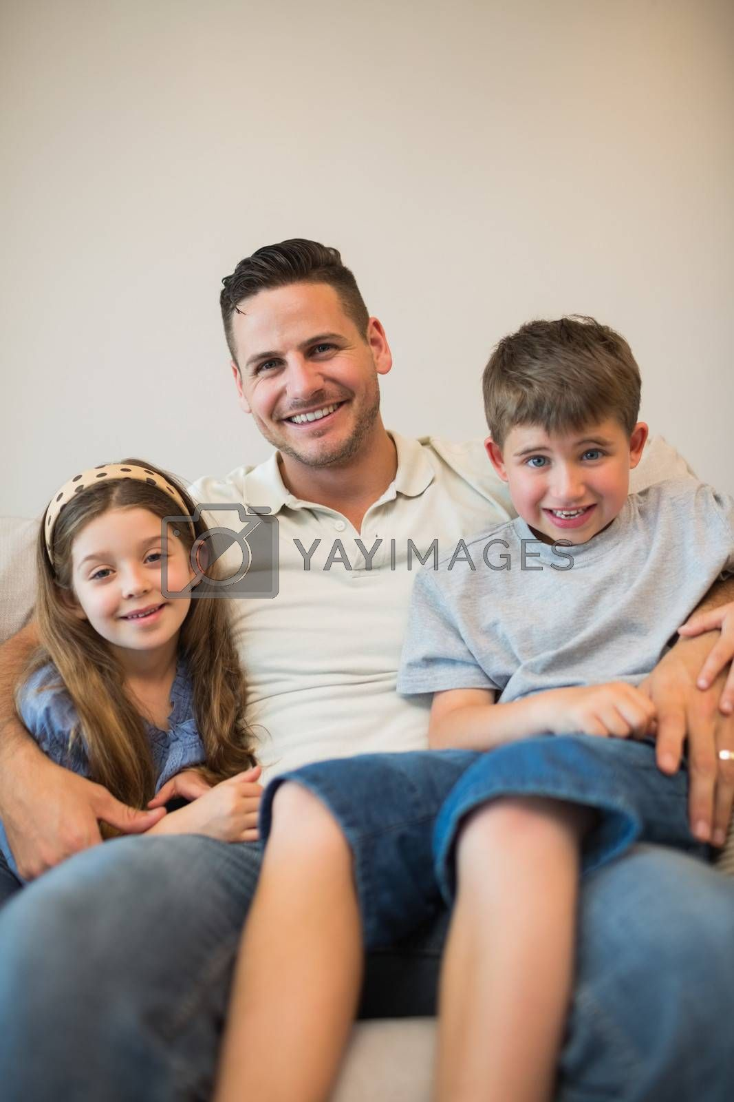 Father with son and daughter smiling on sofa by Wavebreakmedia